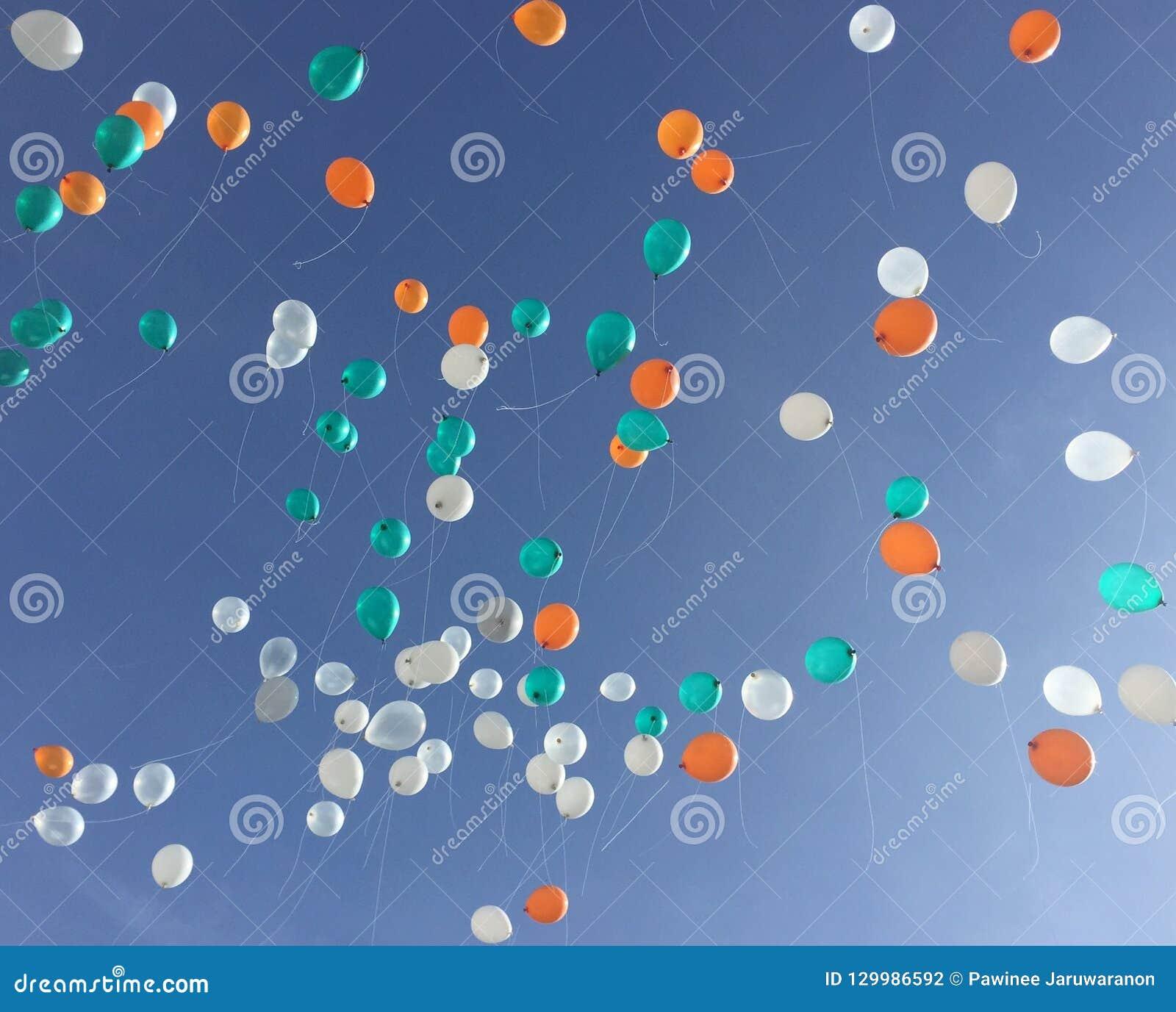 Flotador colorido del globo hasta el cielo azul