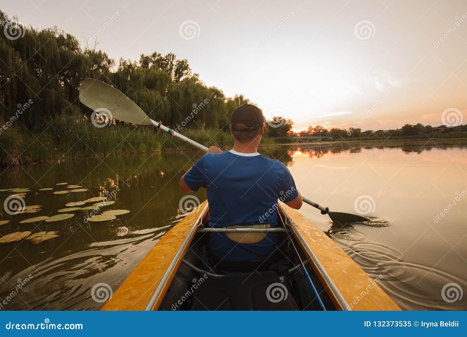 Flotadores del hombre en el kajak deportes acuáticos de la puesta del sol del hombre del kajak