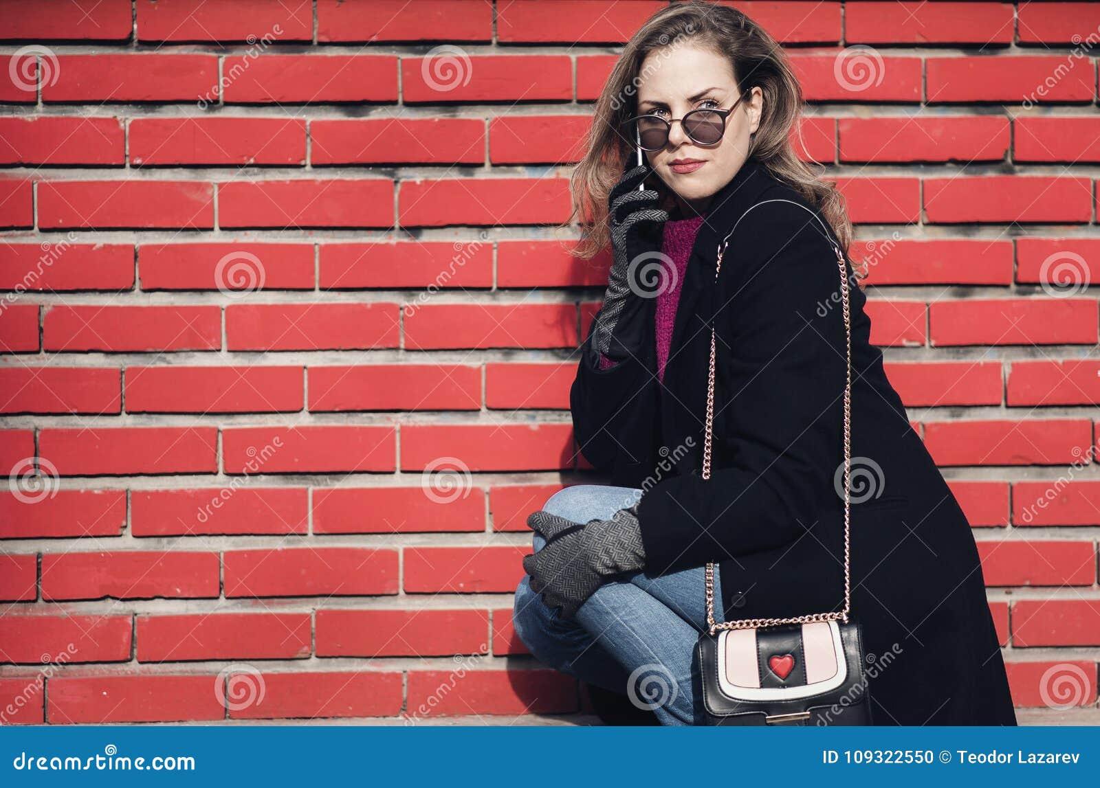 Flott kvinna som utomhus talar på hennes telefon