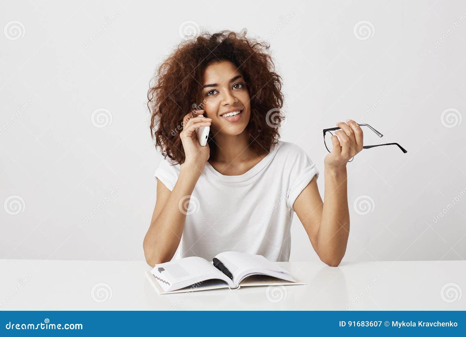 Flott ung afrikansk flicka som tar ett avbrott från hennes studie och att tala till modern på telefonen och att diskutera den nya
