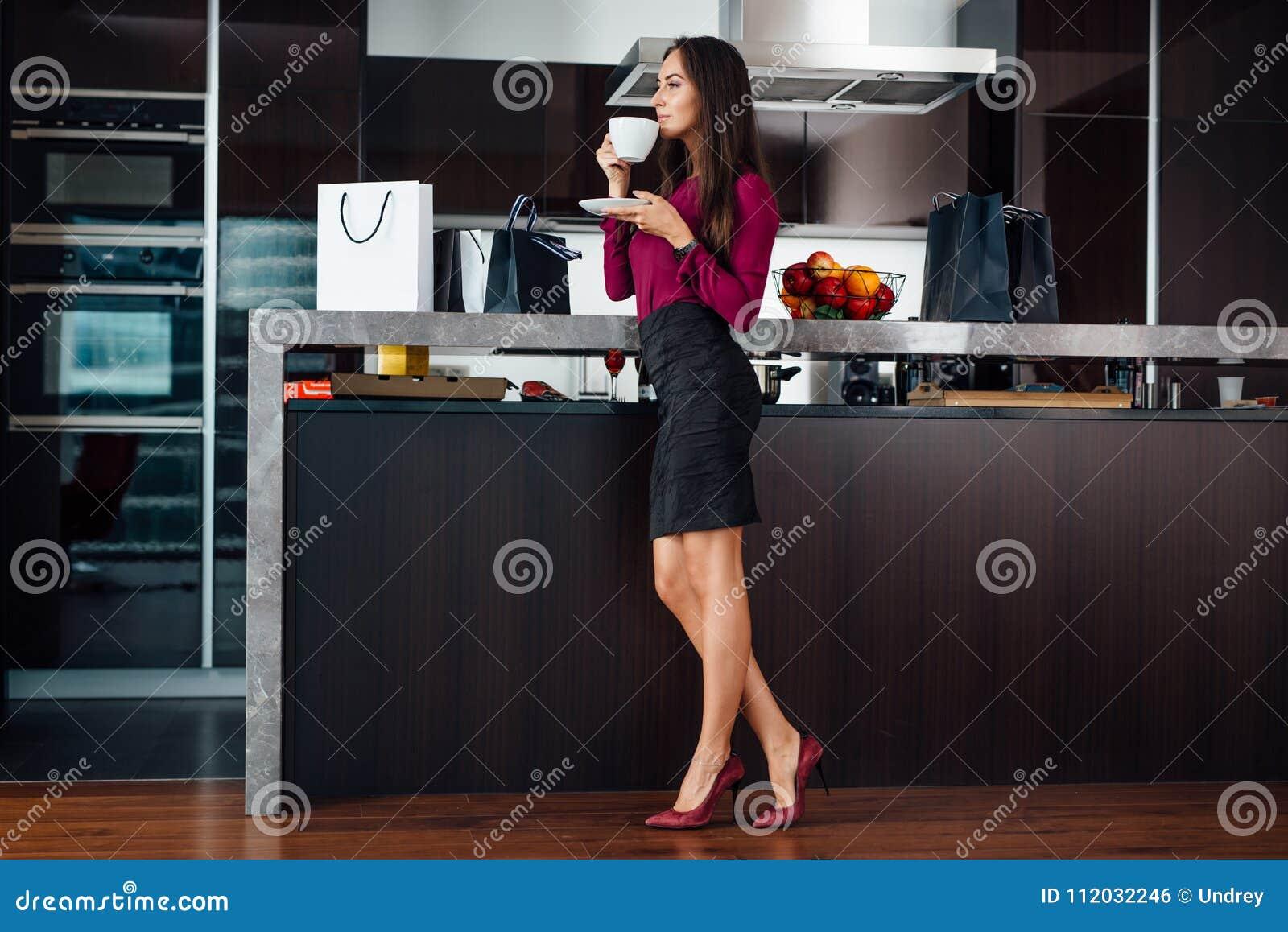 Flott ung latinsk kvinna som dricker kaffeanseende i köket som kopplar av, når att ha shoppat