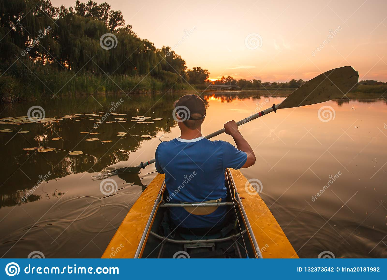 Flotteurs d homme sur le kayak sports aquatiques de coucher du soleil d homme de kayak