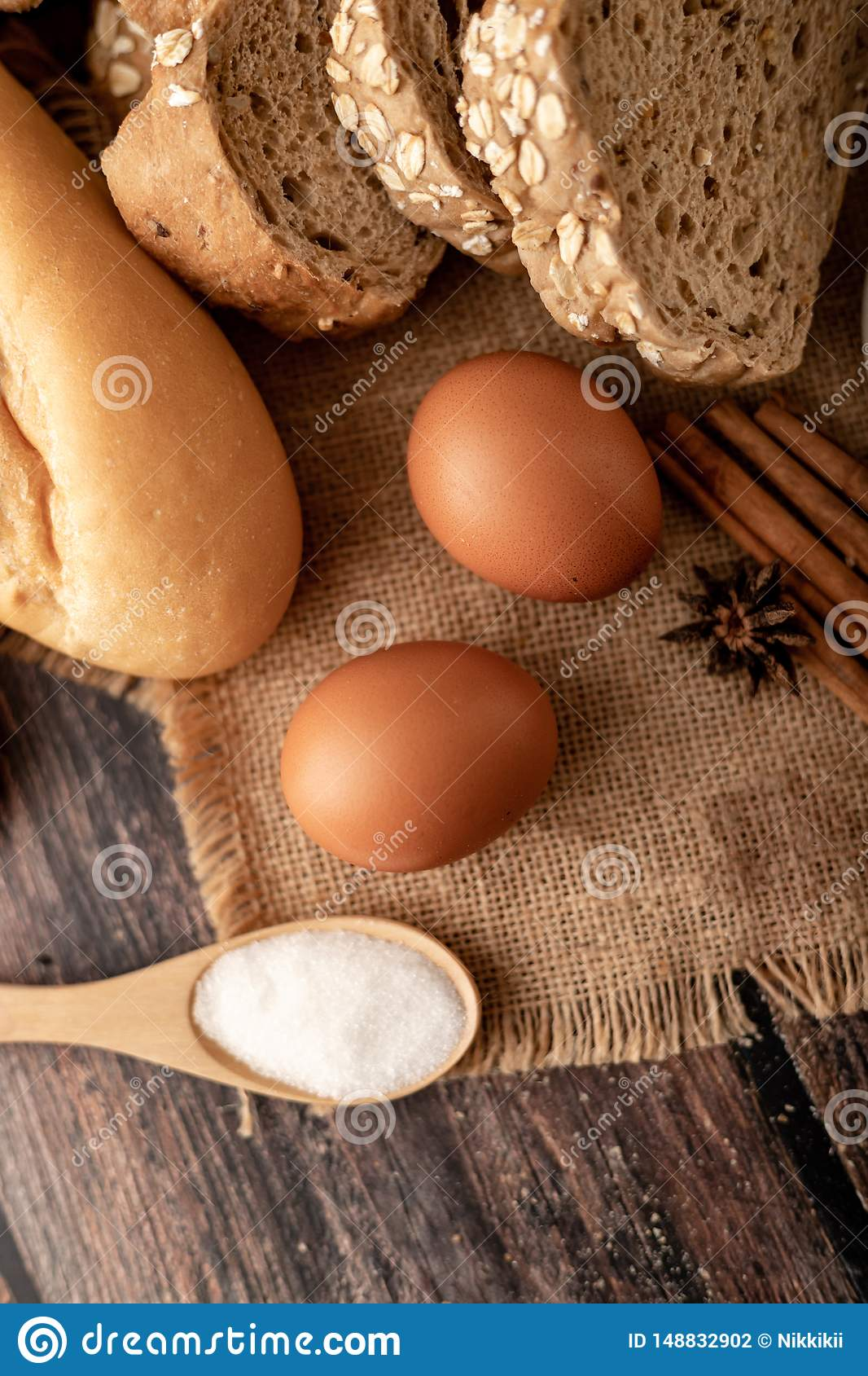 Flour in wooden spoon and eggs on the sack