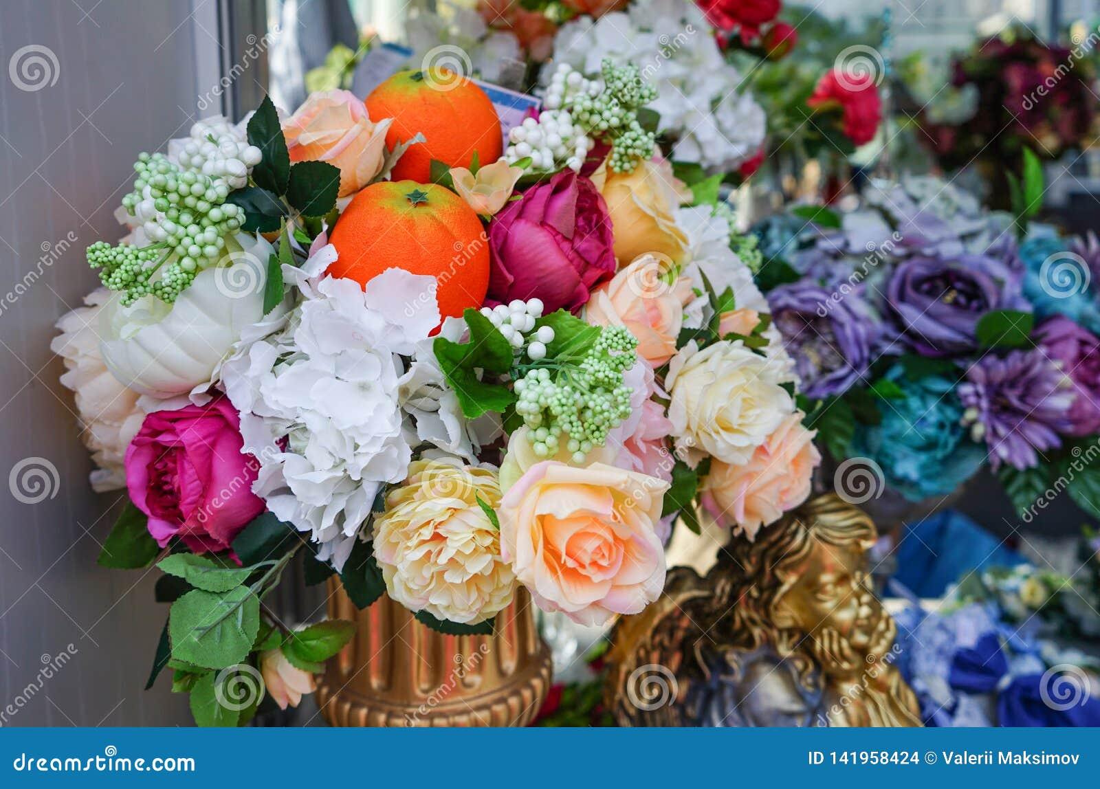 Flower arrangement of artificial flowers and oranges