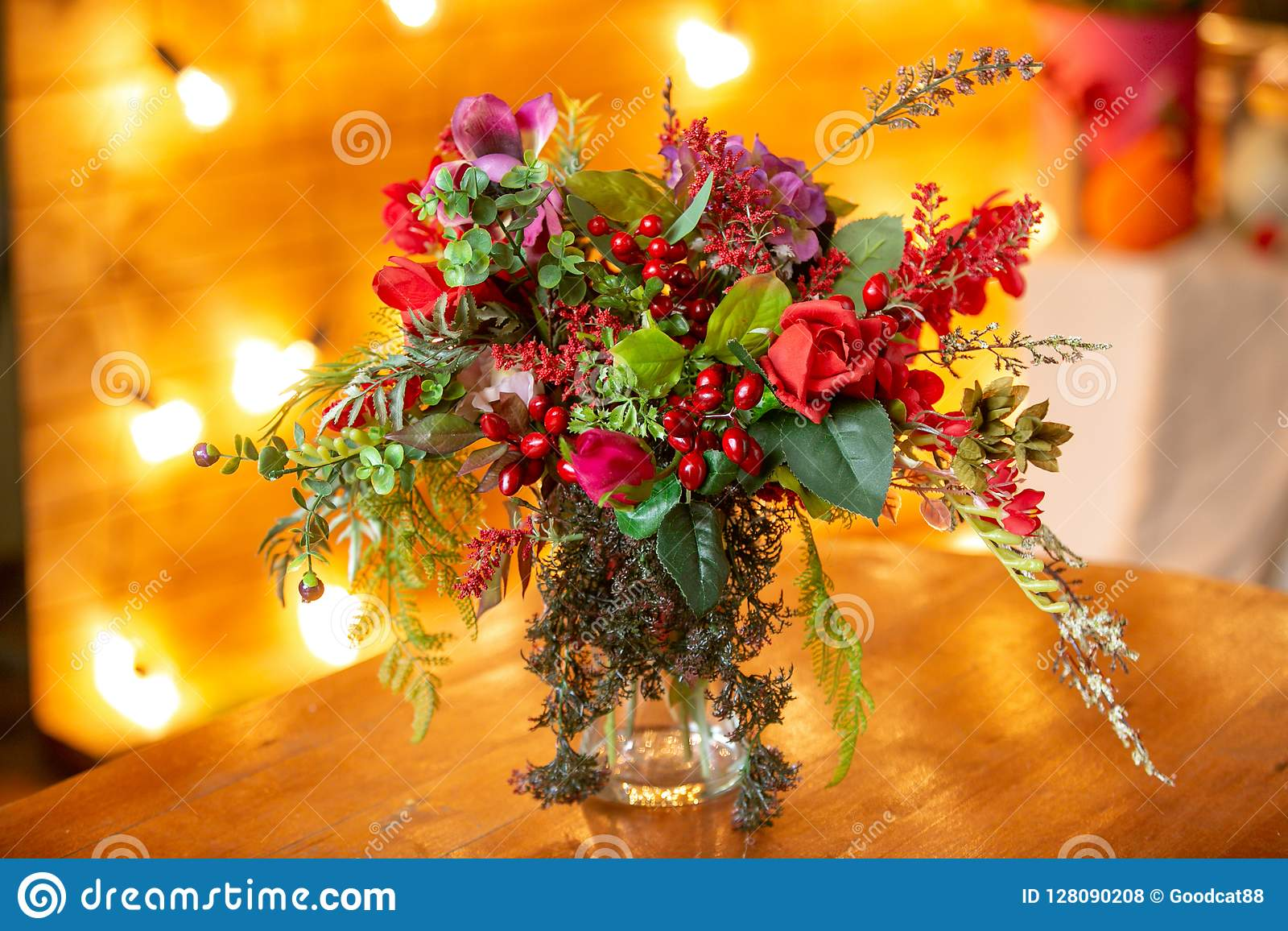 Flower arrangement with red berries, red roses and greens on the table
