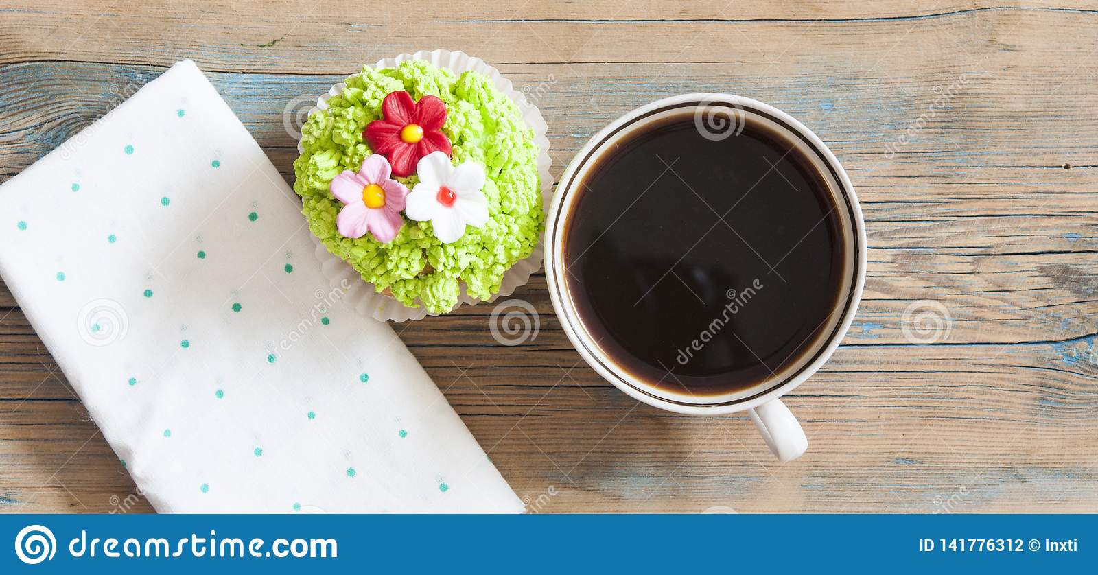 Flower spring cupcake with hot coffee cup on wooden table