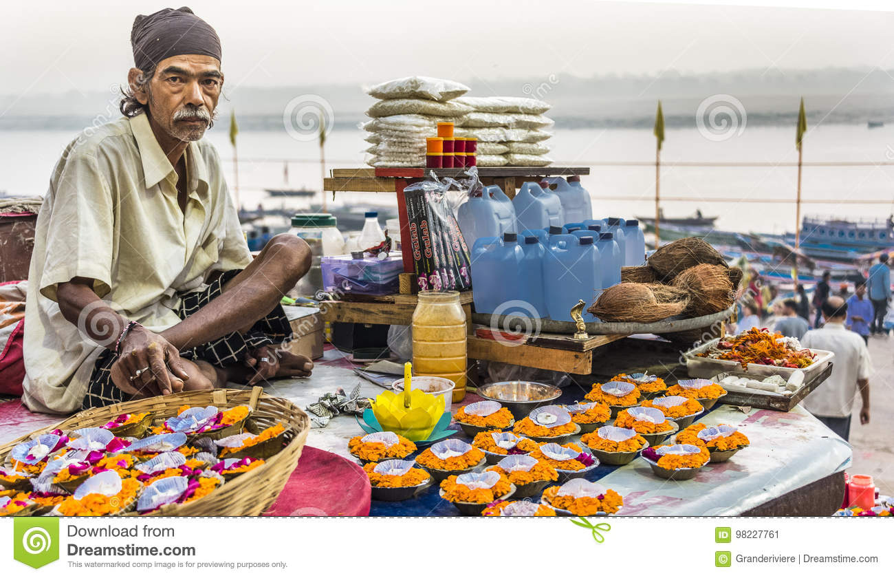 Download A Flower Vendor Sits On A Platform Above The Ganges River With Legs Crossed Selling His Flowers And Candles In Varanasi Editorial Photo - Image of culture, bunch: 98227761