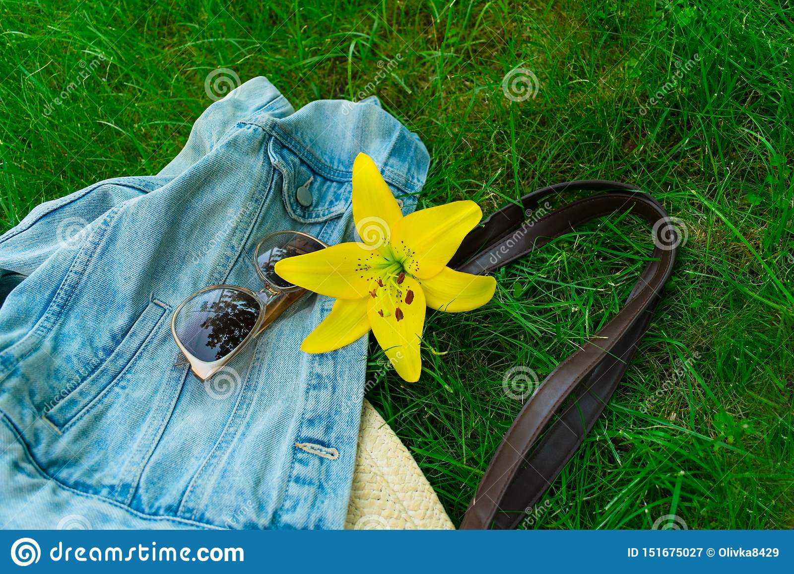 A flower of a yellow lily sunglasses and a summer bag on a green grass. Concept of summer walks.