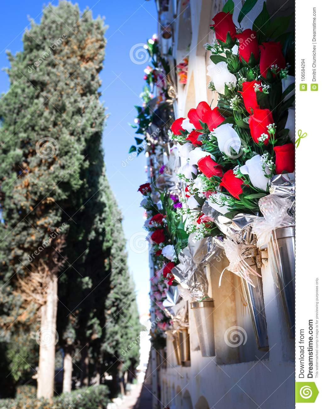 flowers in the cemetery near the wall with the burial stock photo