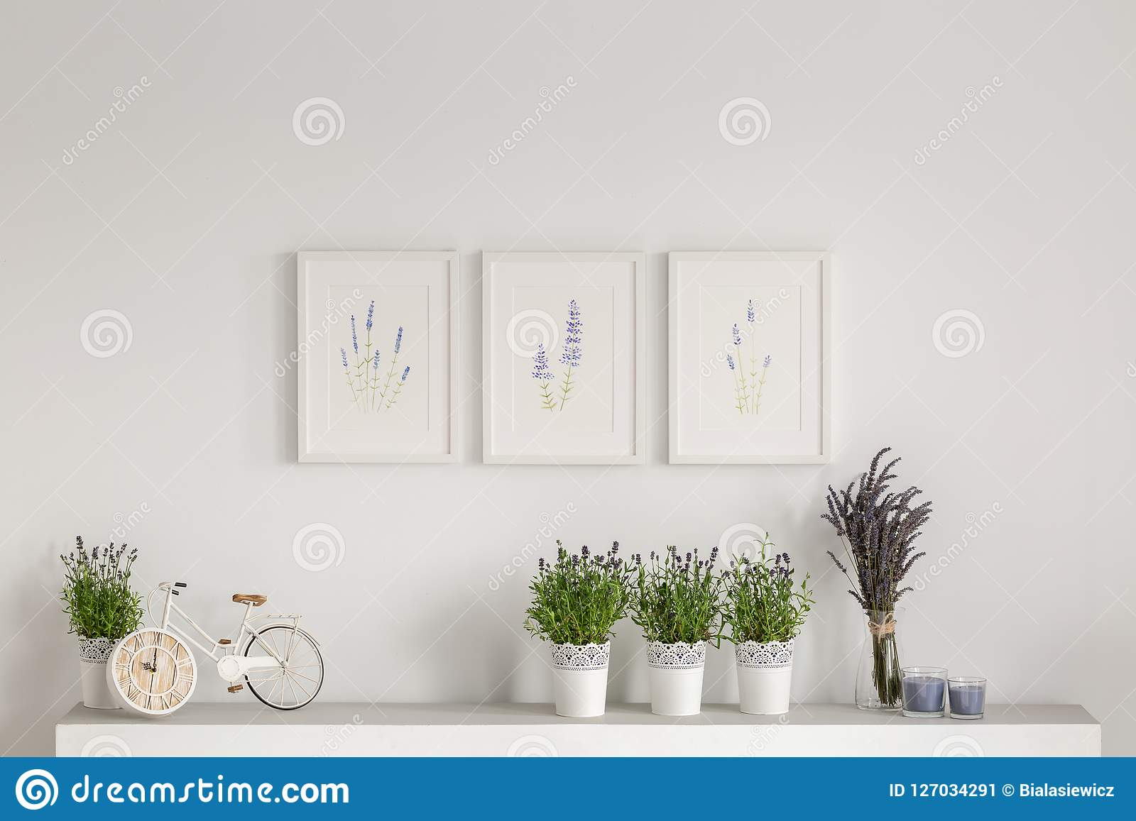 Flowers on cupboard against white wall with posters in minimal living room interior. Real photo