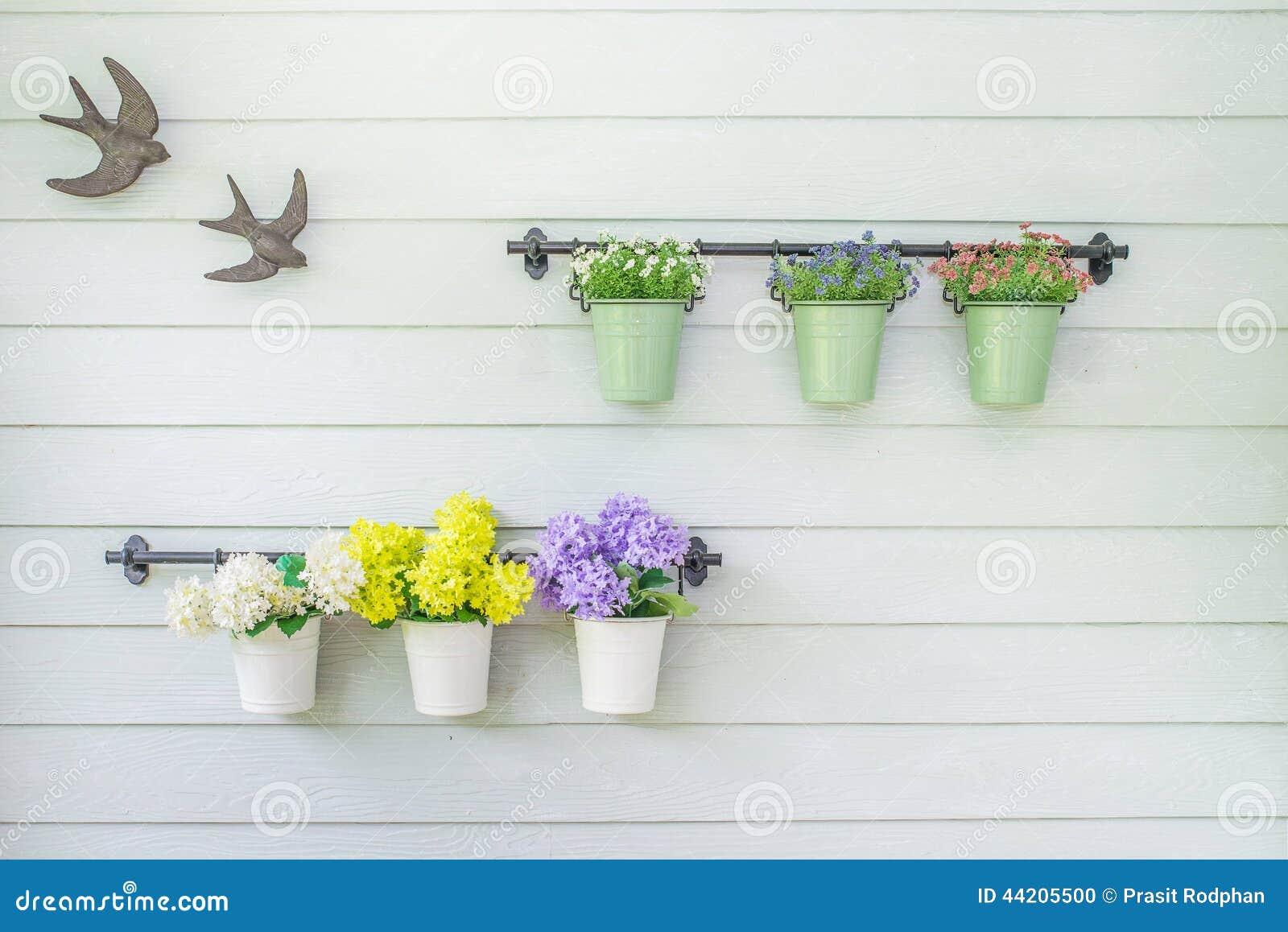 Flowers in flowerpot on wooden wall