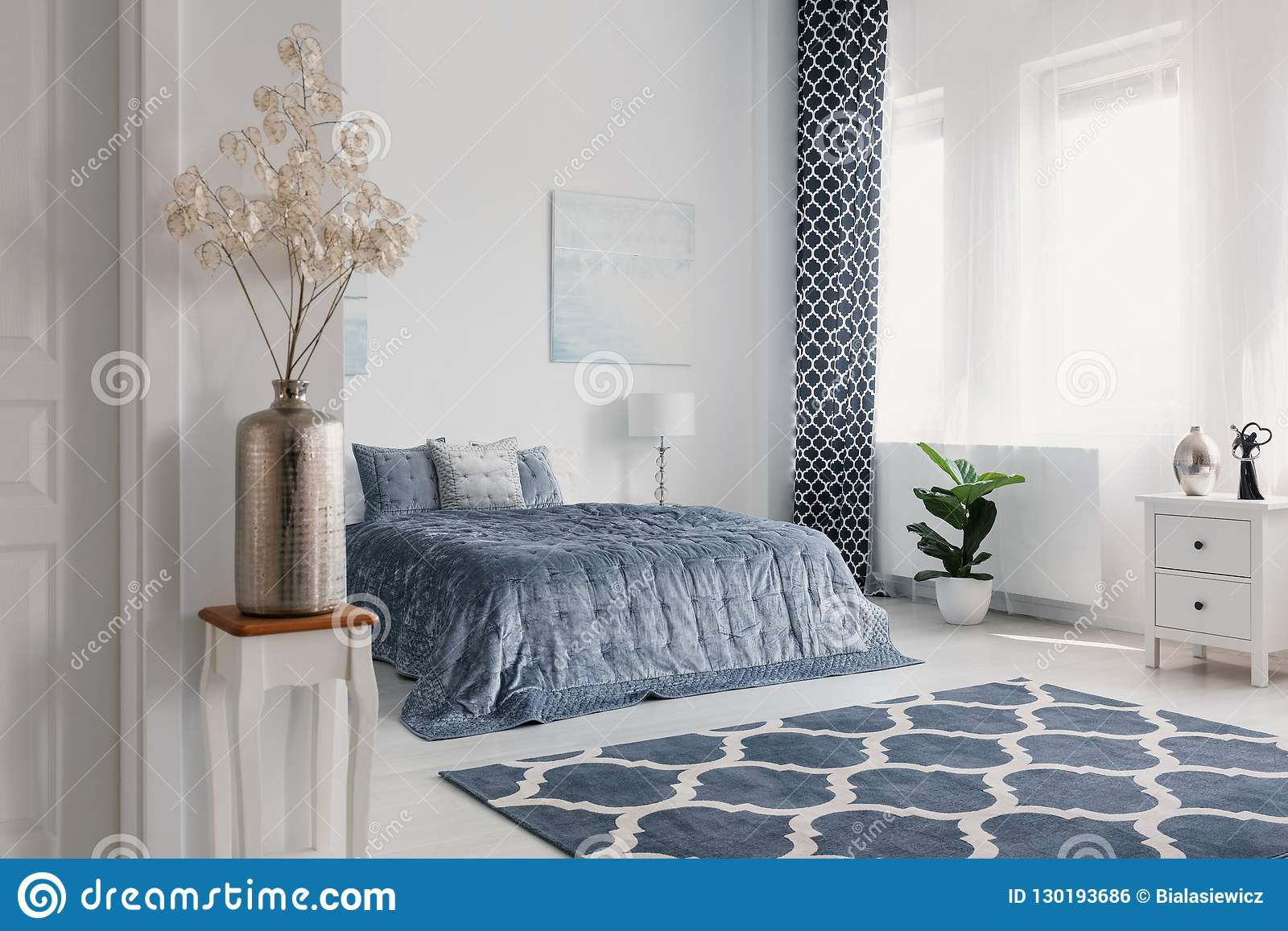 Flowers in gold vase in white bedroom interior with patterned carpet in front of blue bed. Real photo