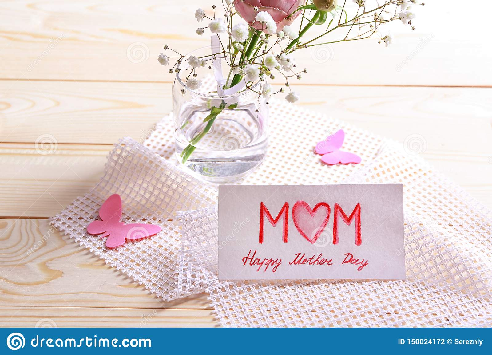 flowers and handmade card for mother s day on wooden table