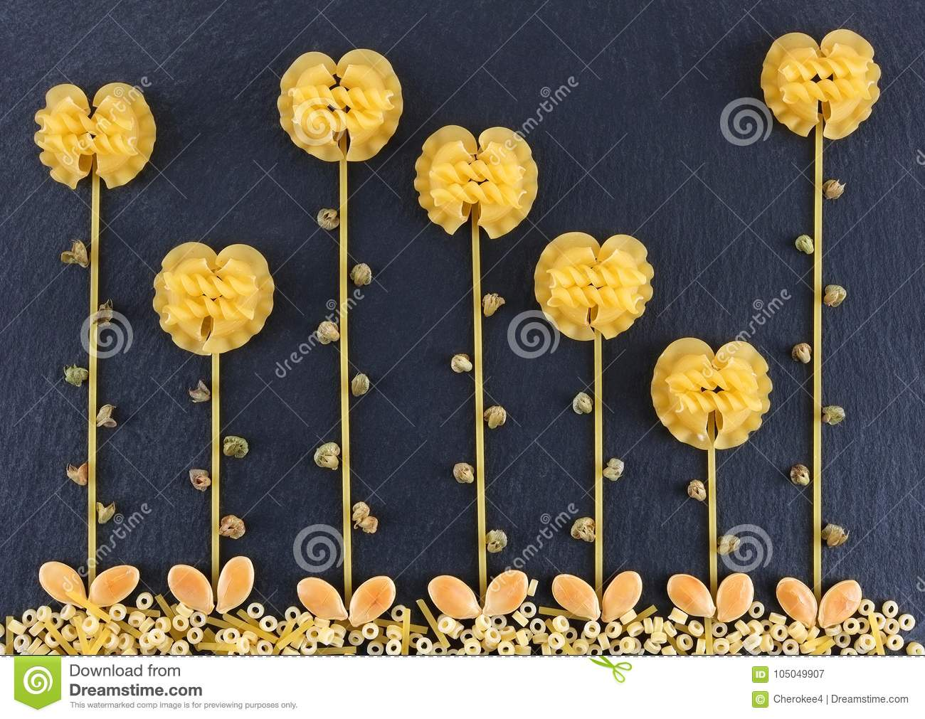 Flowers made out of various pasta on the dark slate background, topview. Flowers made from pasta.