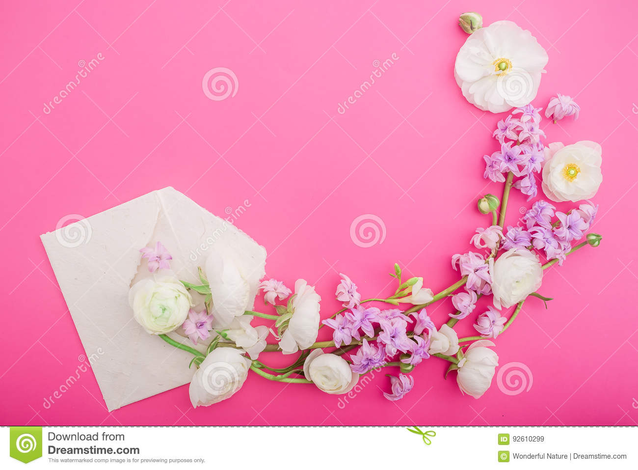 Flowers and paper envelope on pink background. Flat lay, top view. Floral round frame