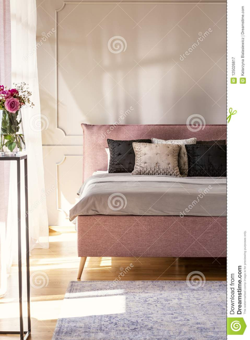 Flowers In Pink Bedroom Interior With Bed With Cushions Against ...