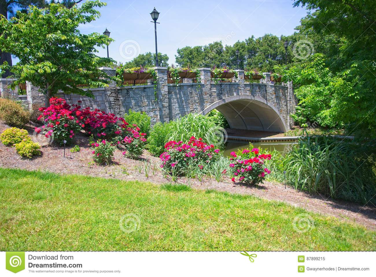 Flowers enclosing the stone bridge over the canal passing through the Norfolk Botanical Gardens.