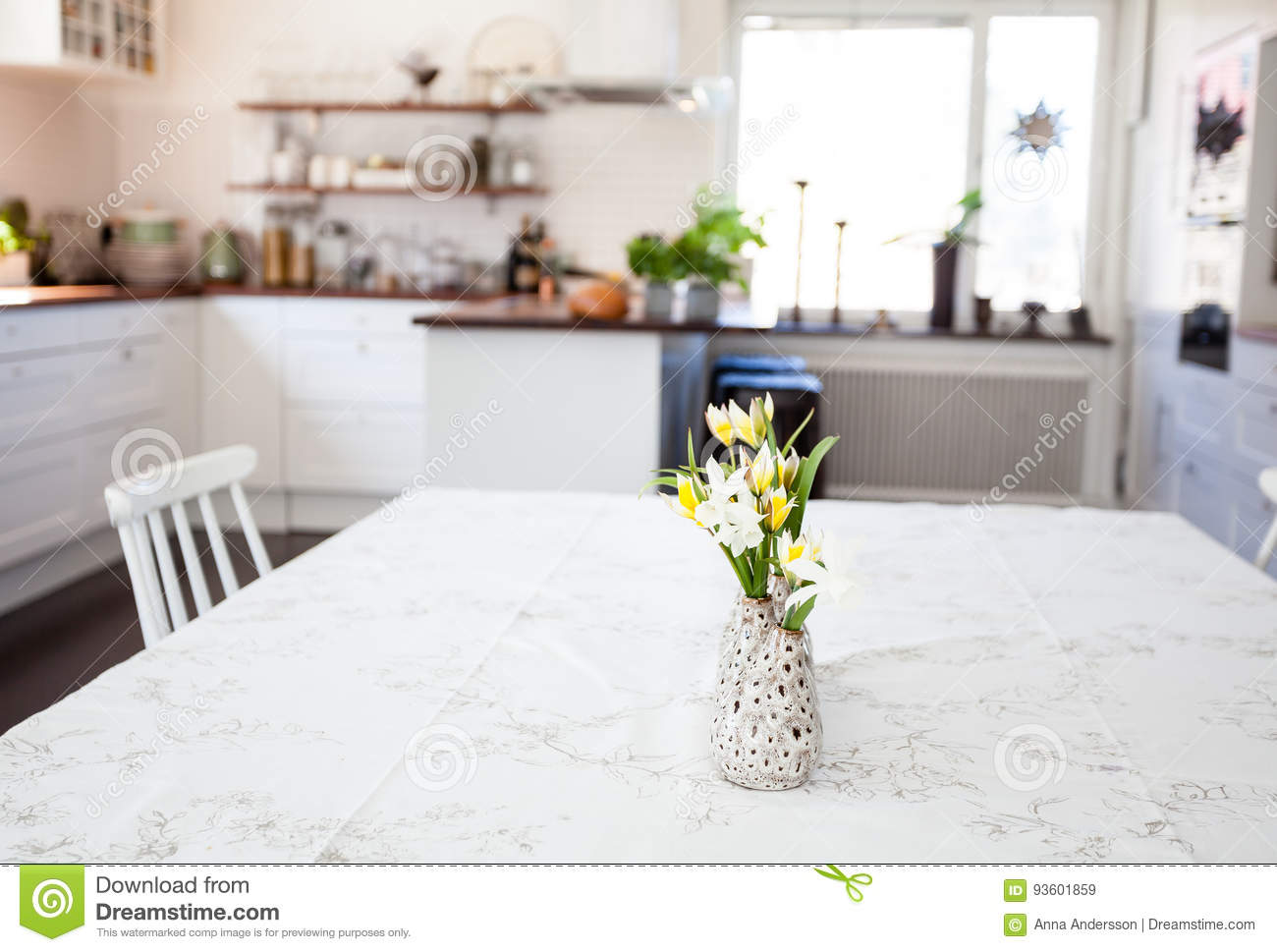 Flowers at the table in the foreground kitchen blurred in the background