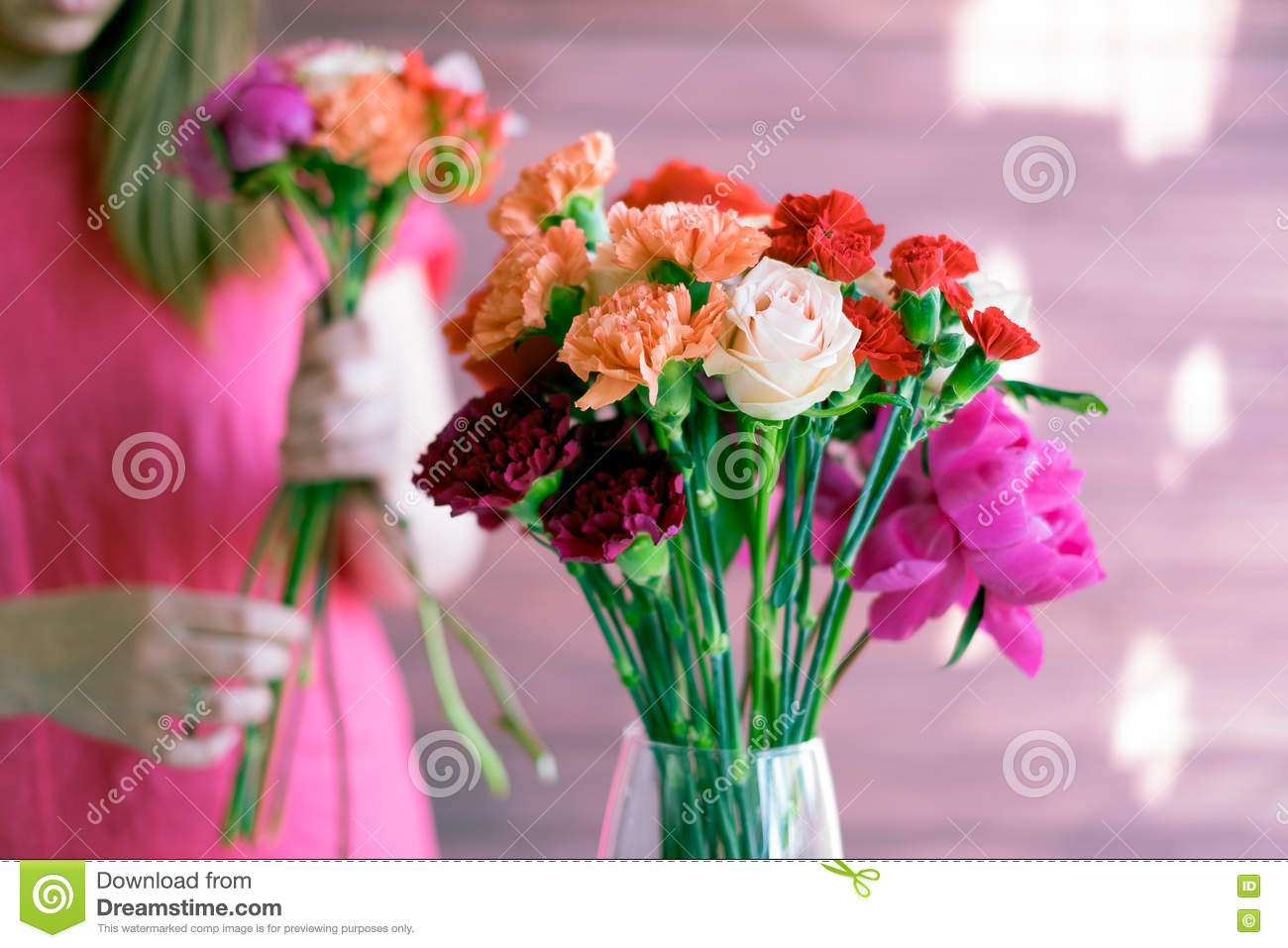 Flowers in a vase and a girl in the background