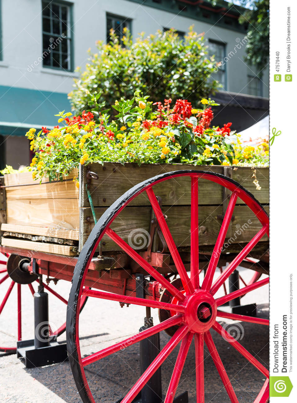 An old wood cart with large red wagon wheel used as a garden planter