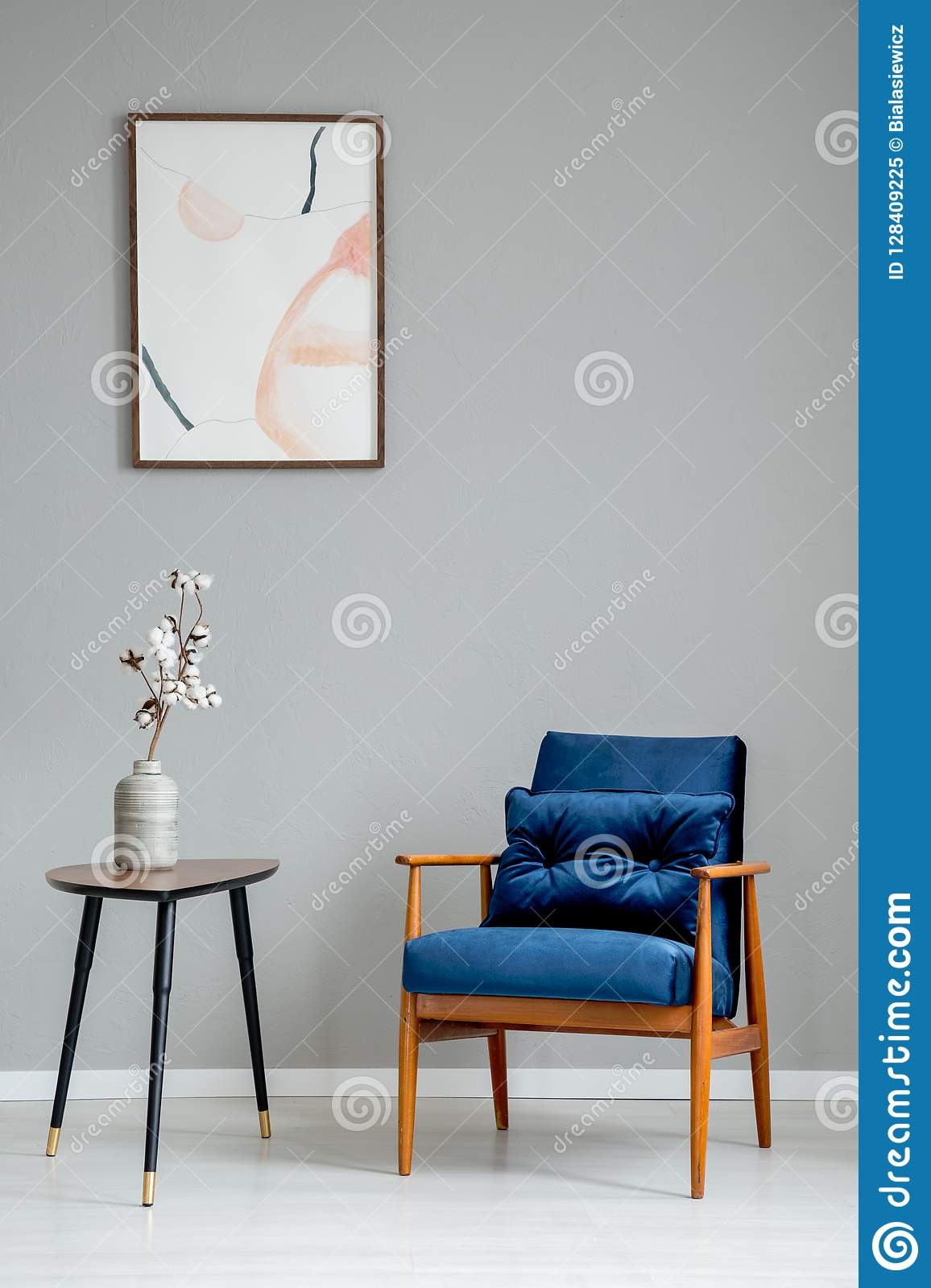 Flowers on wooden table next to blue armchair in grey apartment interior with poster.