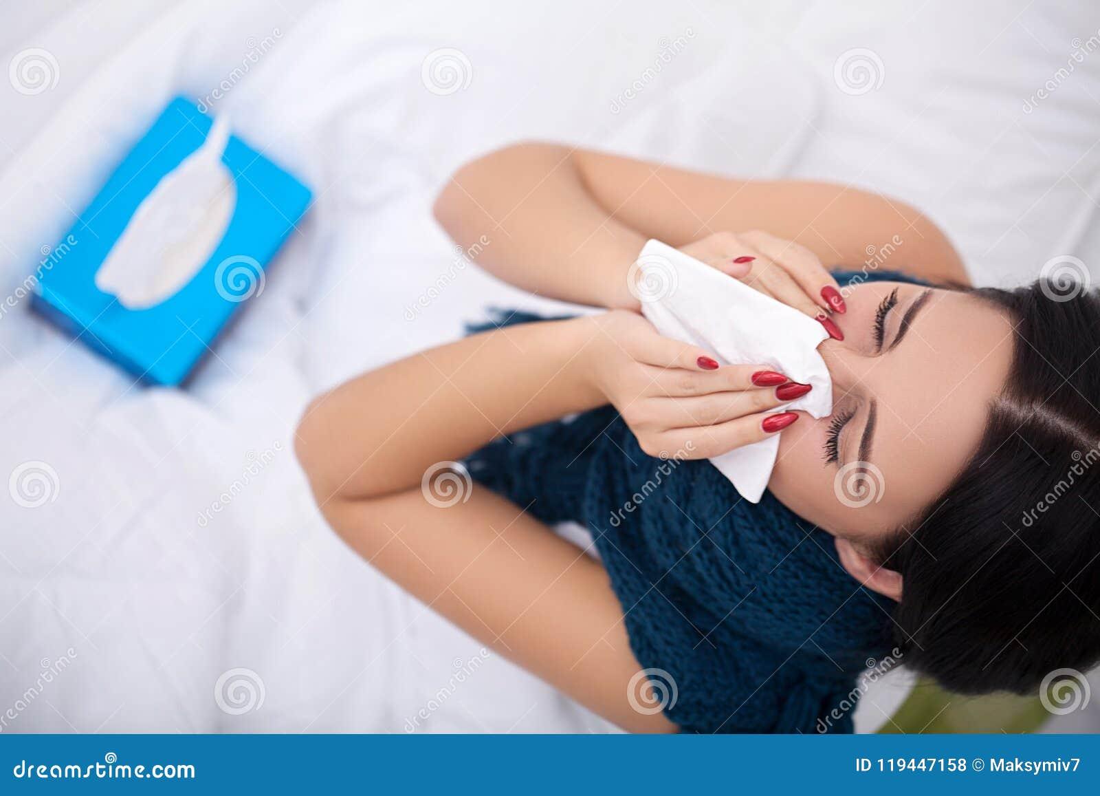 Flu Donna che soffre dal freddo che si trova a letto con il tessuto