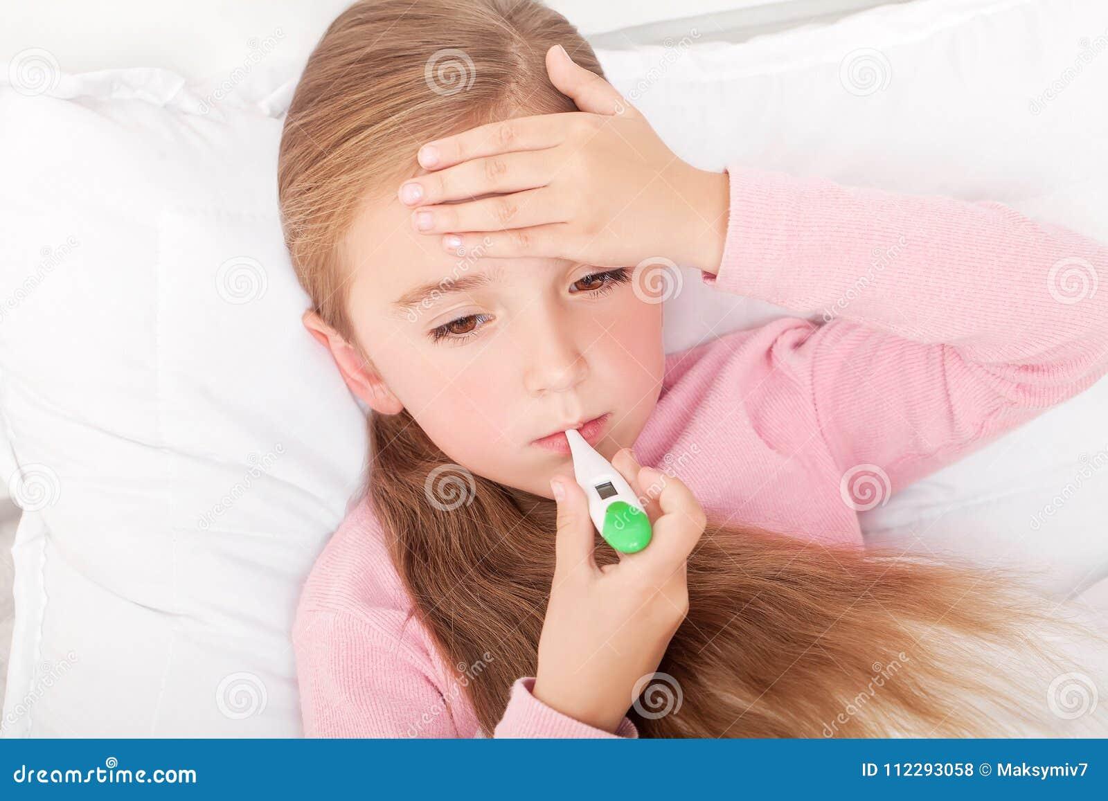 Flu Ragazza che si trova a letto con un termometro