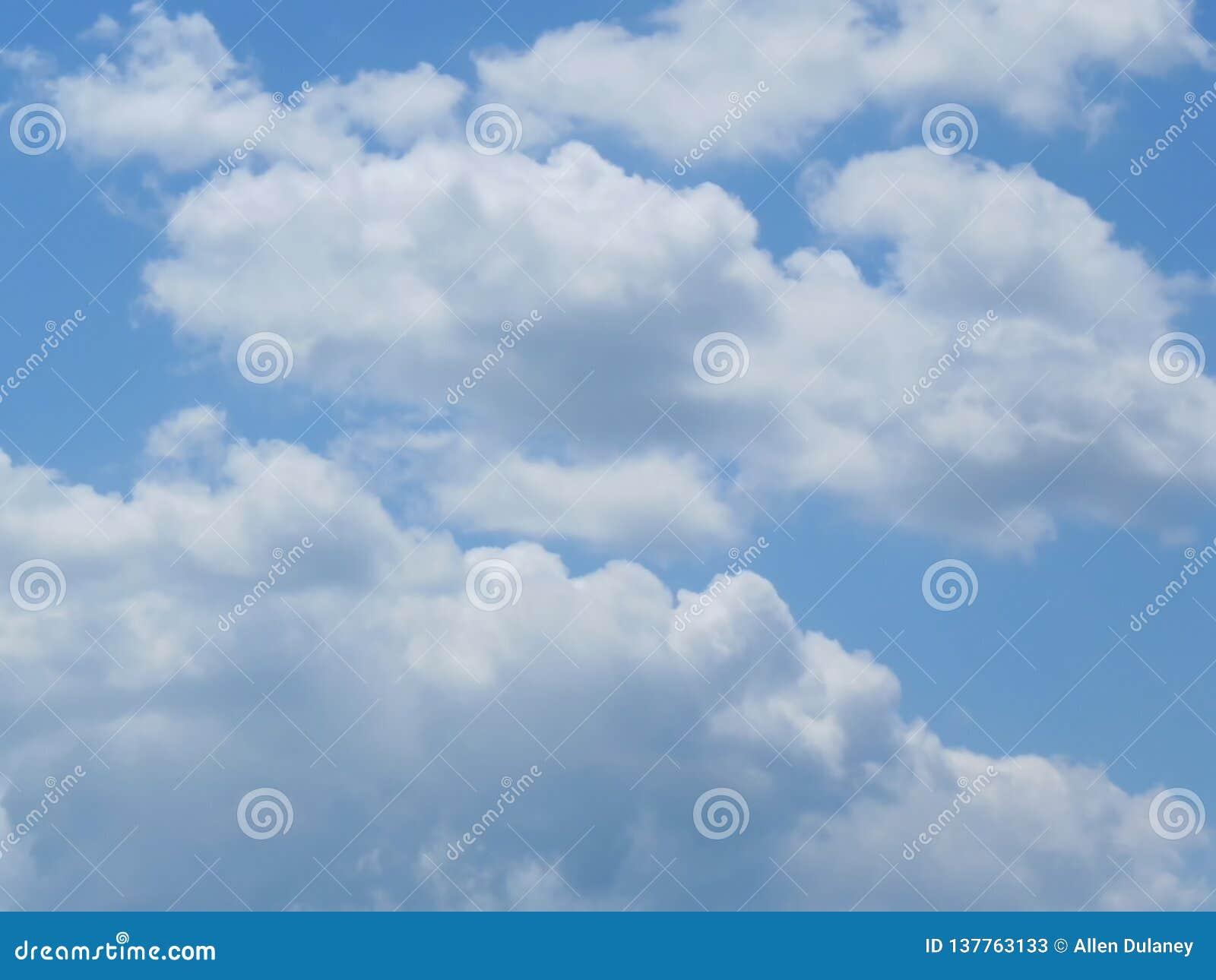 Fluffly chmurnieje w niebieskim niebie