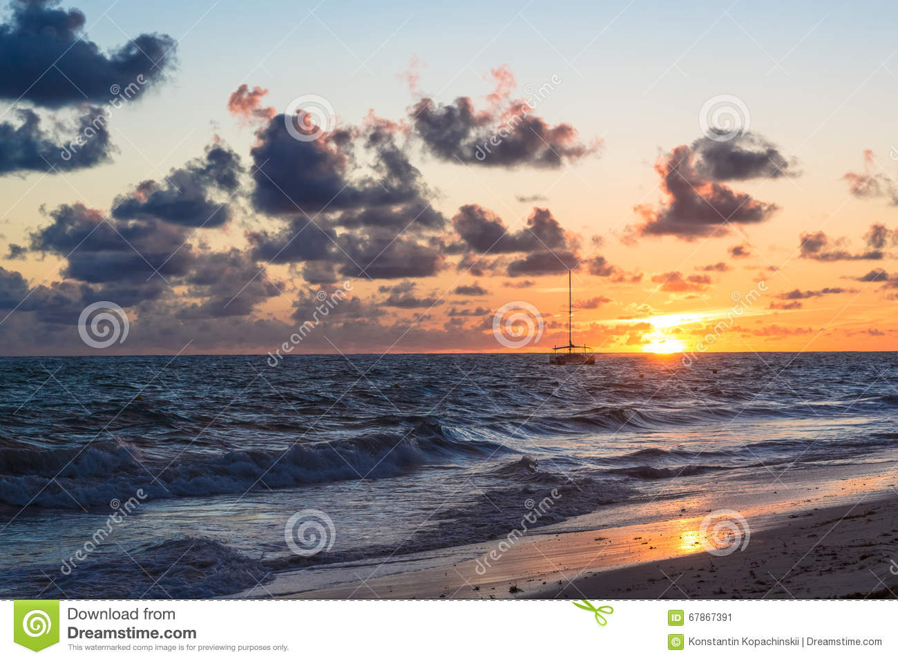 Fluffy dark clouds floating over turbulent ocean waters on sandy beach shore