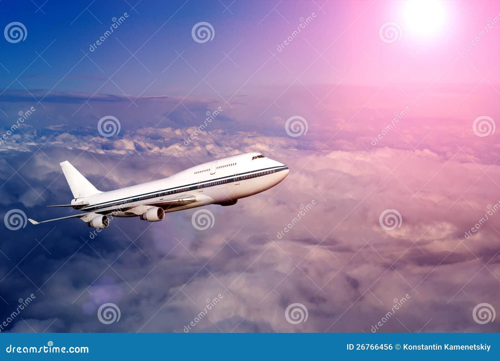 Fluggastflugzeug in den Wolken am Sonnenuntergang oder an der Dämmerung
