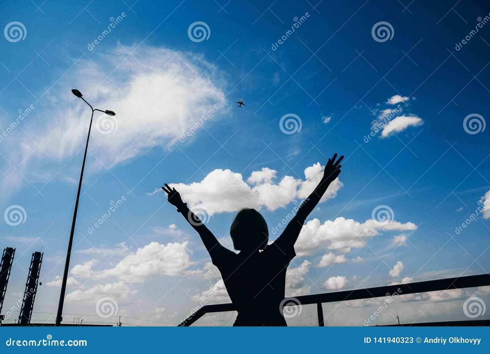 Flugzeug und Schattenbildfrau auf dem Himmelhintergrund Landschaft einer Stadt mit einer Mädchenstellung mit den Armen angehoben