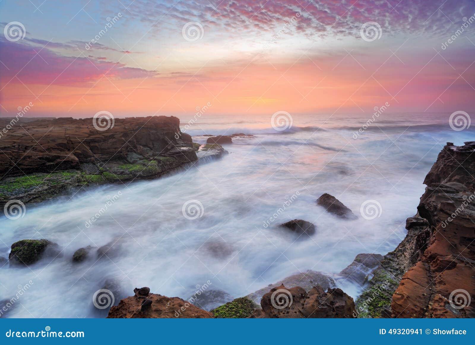 Flujos imponentes de la salida del sol y del océano sobre rocas de marea