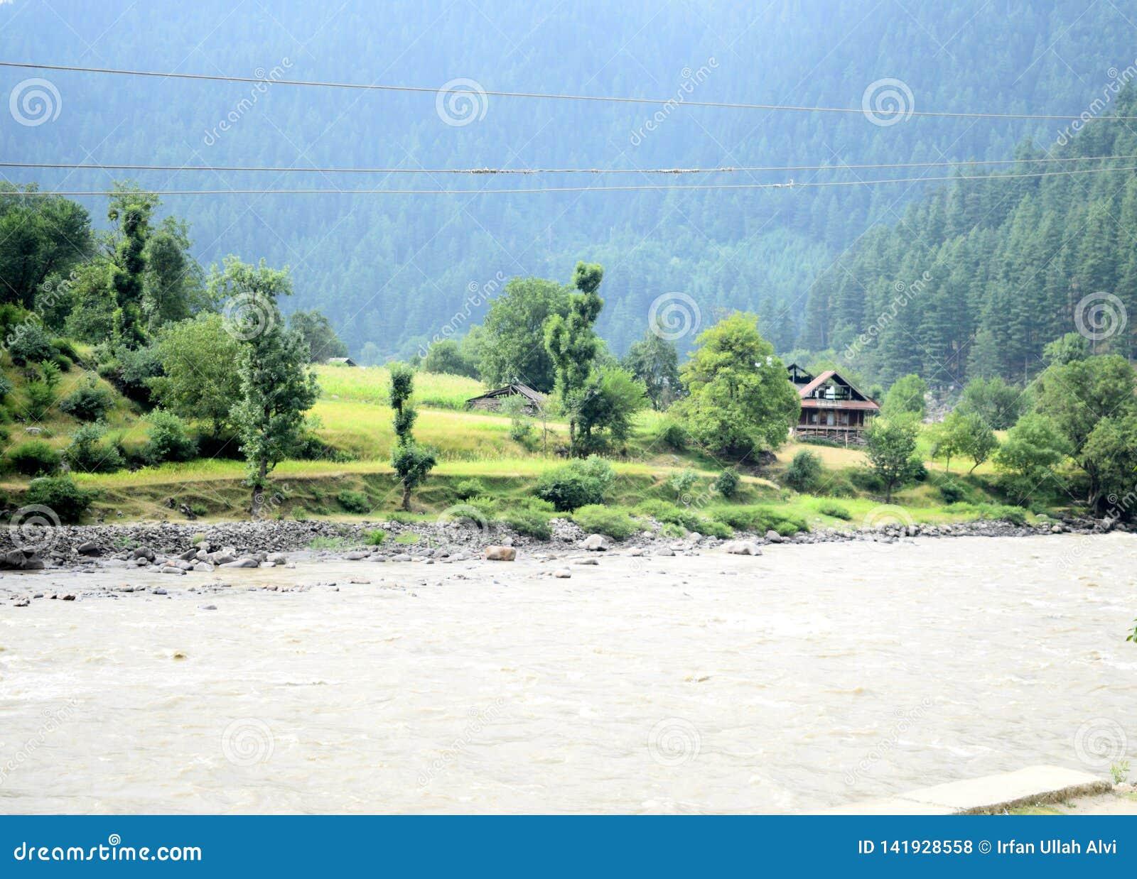 Flussbank mit kleinem Dorf und enorme wilde Berge auf der Rückseite Gebirgstal mit einem Fluss und einem Dorf