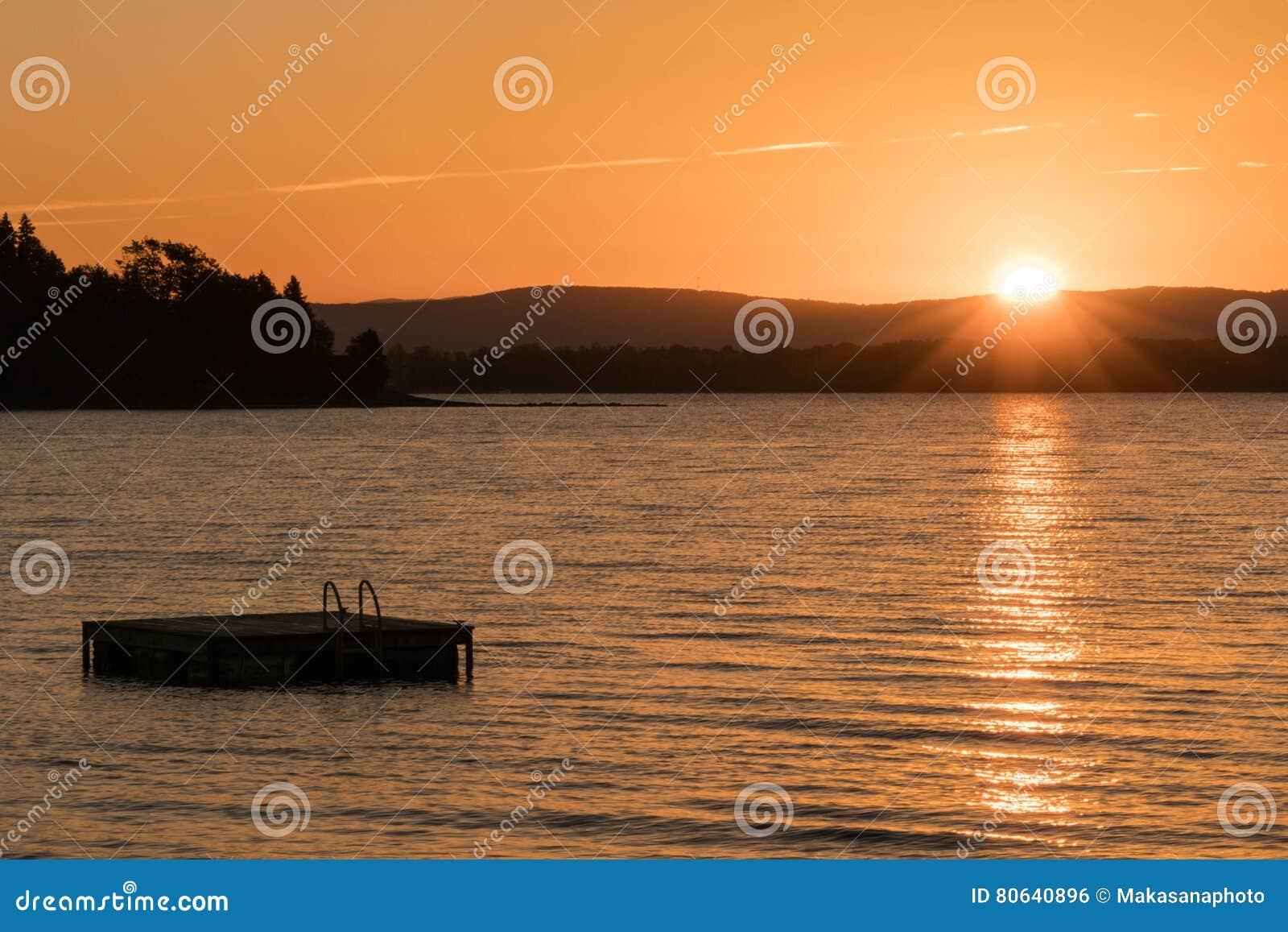 Flutuador e lago nadadores em Vermont no por do sol