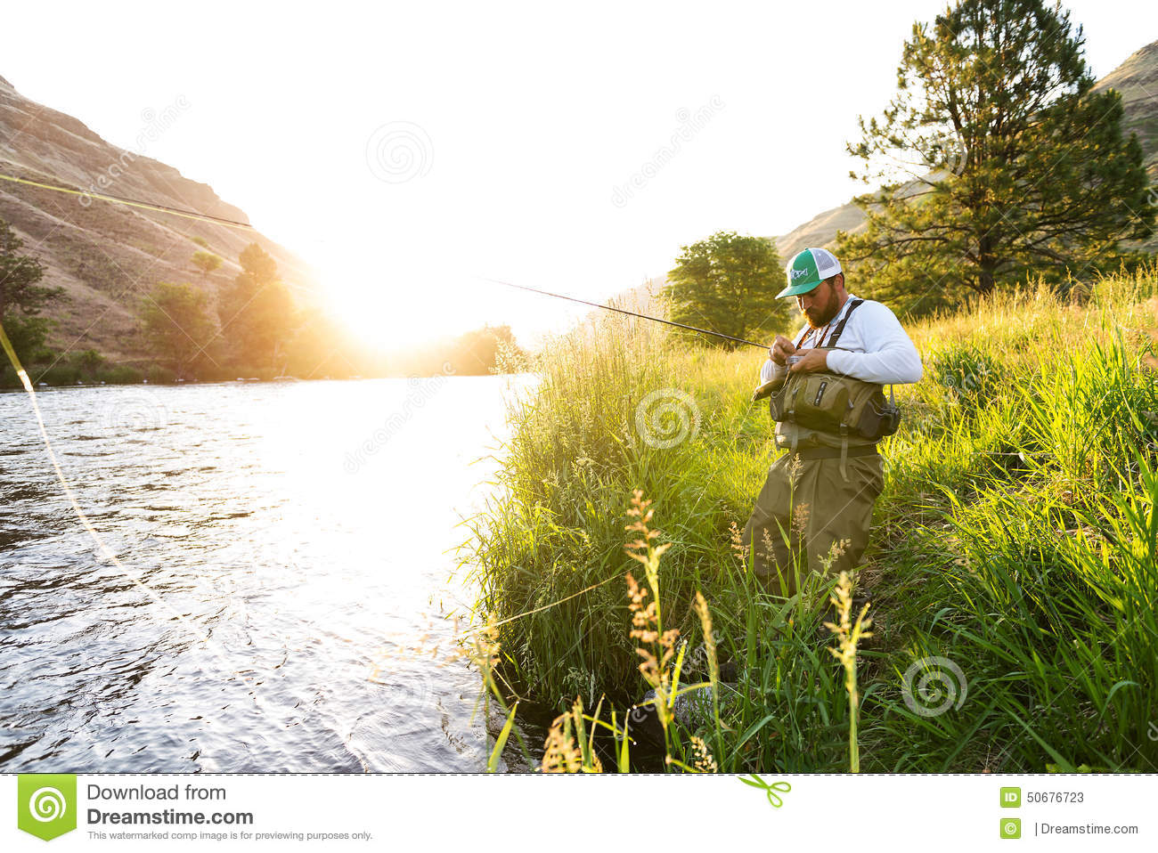 Fly Fisherman On The River Bank At Sunrise Stock Image