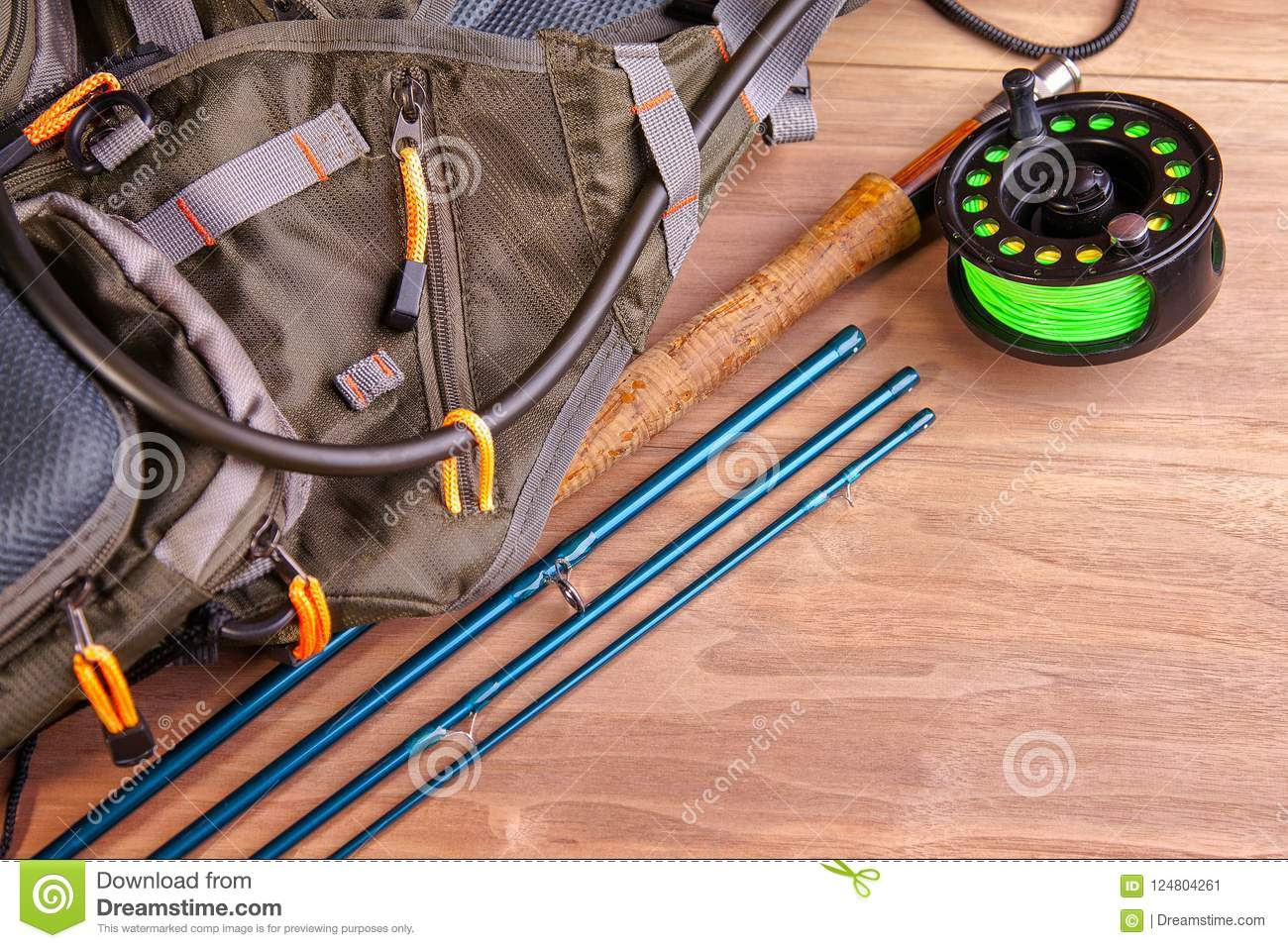 Fly Fishing Rod With A Coil And Flies Lie On Old Wooden Boards
