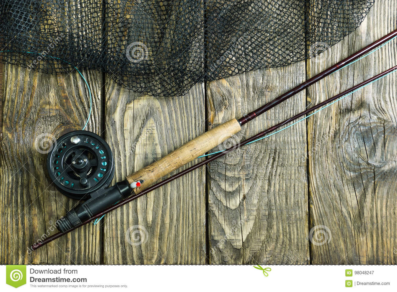 Fly Fishing Rod Flie And A Landing Net On The Old Wooden Table All