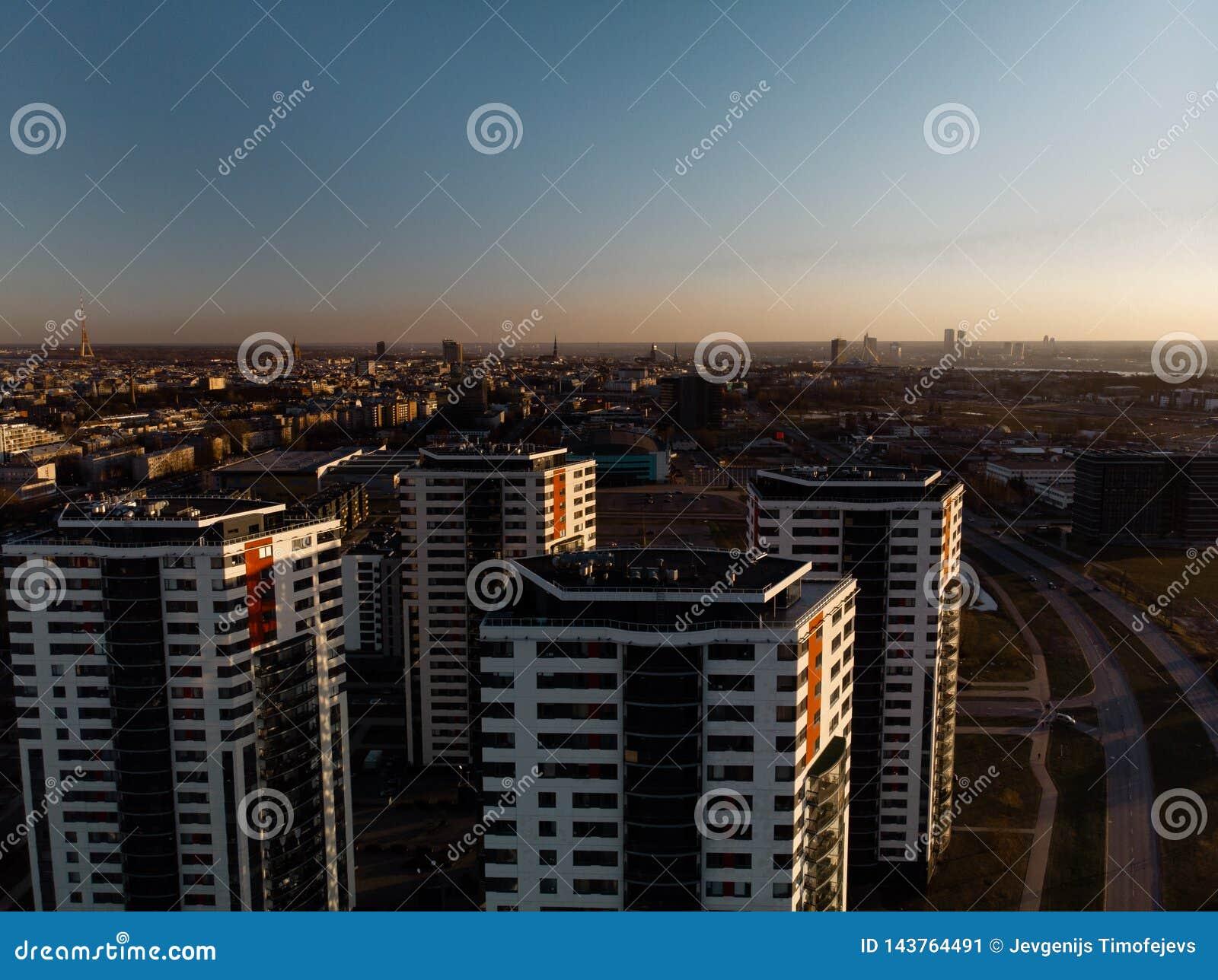 Flyg- dramatisk landskapsolnedgång med en sikt över skyskrapor i Riga, Lettland - det gamla stadcentret är synligt i