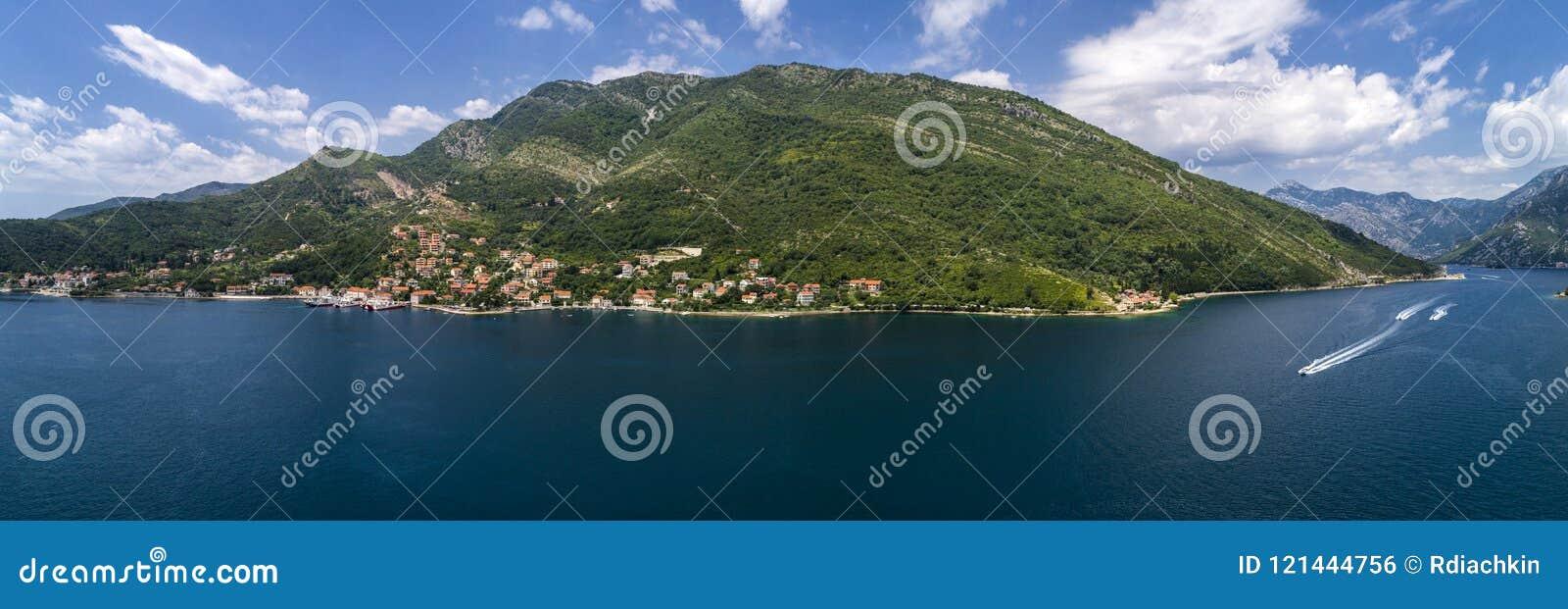 Flyg- panorama- härlig sikt från ovannämnt till den Kotor fjärden och stamgästpassagerarfärjan från Lepetane till Kamenari vid en