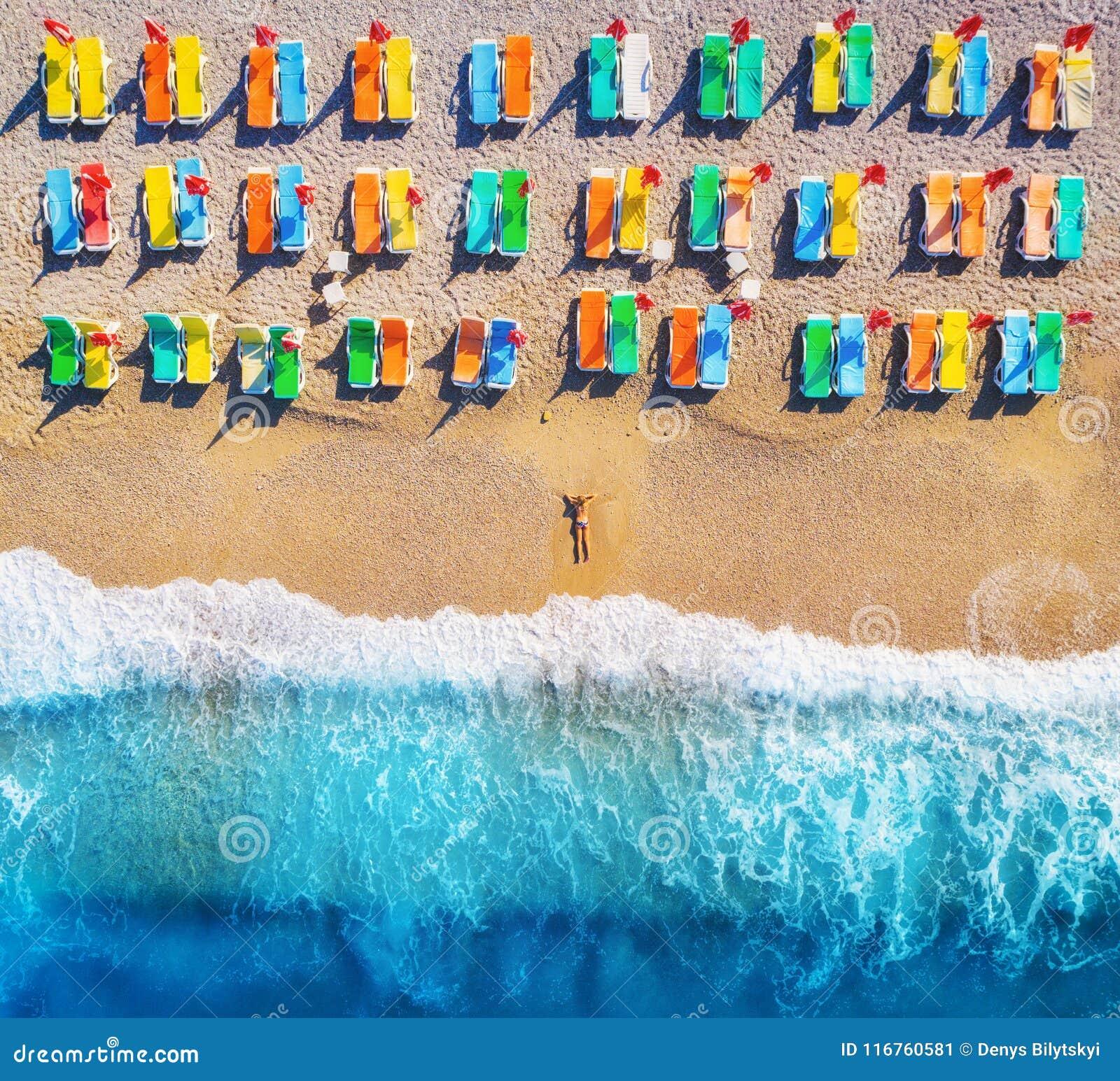 Flyg- sikt av den liggande kvinnan på stranden med färgrika chaise-vardagsrum