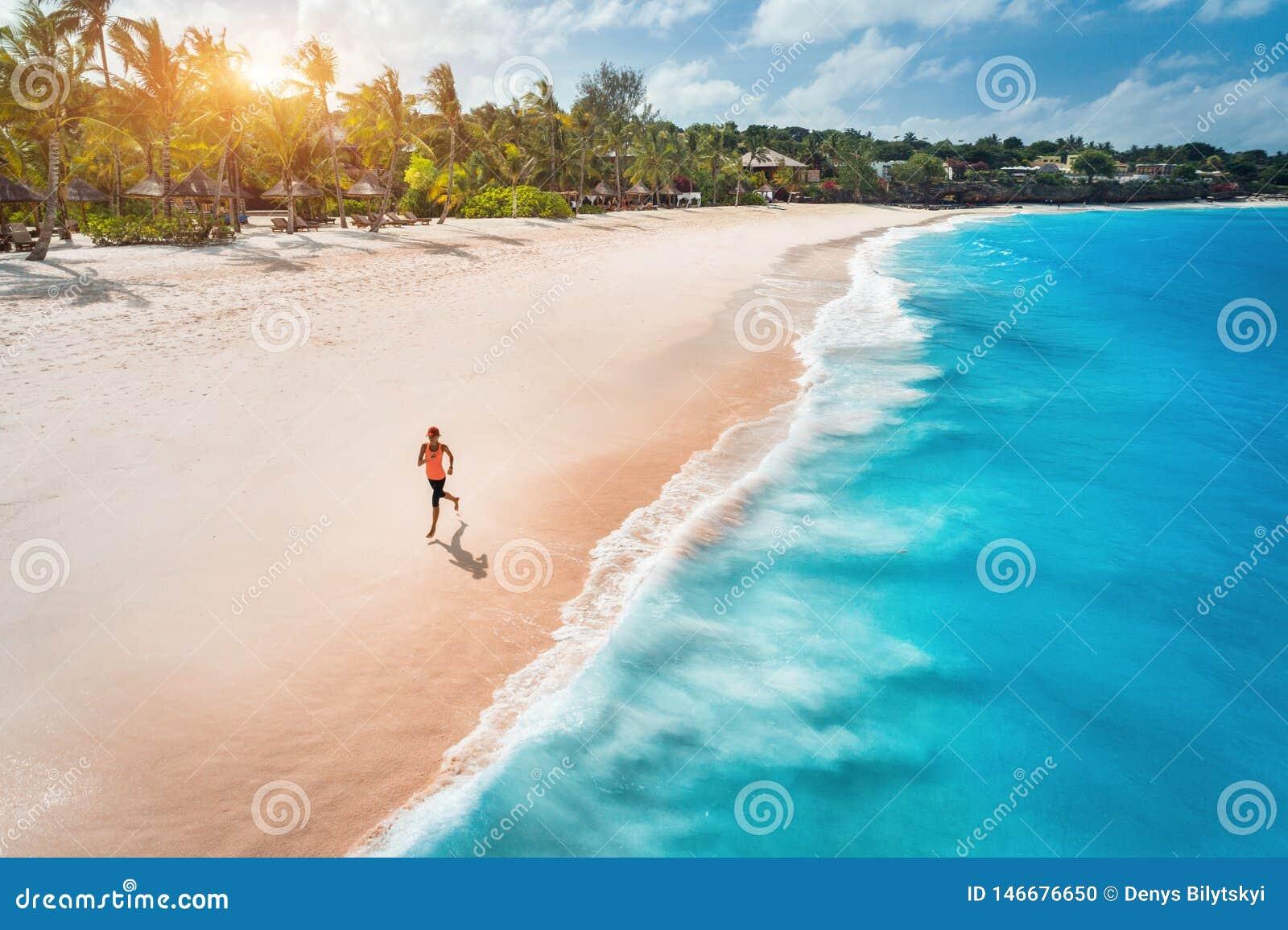 Flyg- sikt av den rinnande unga kvinnan p? den sandiga stranden