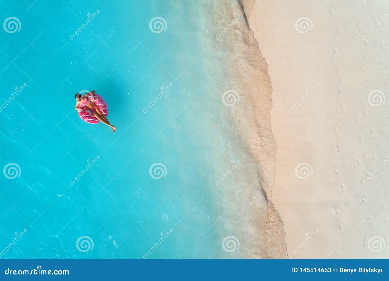 Flyg- sikt av en simma kvinna i havet p? solnedg?ngen