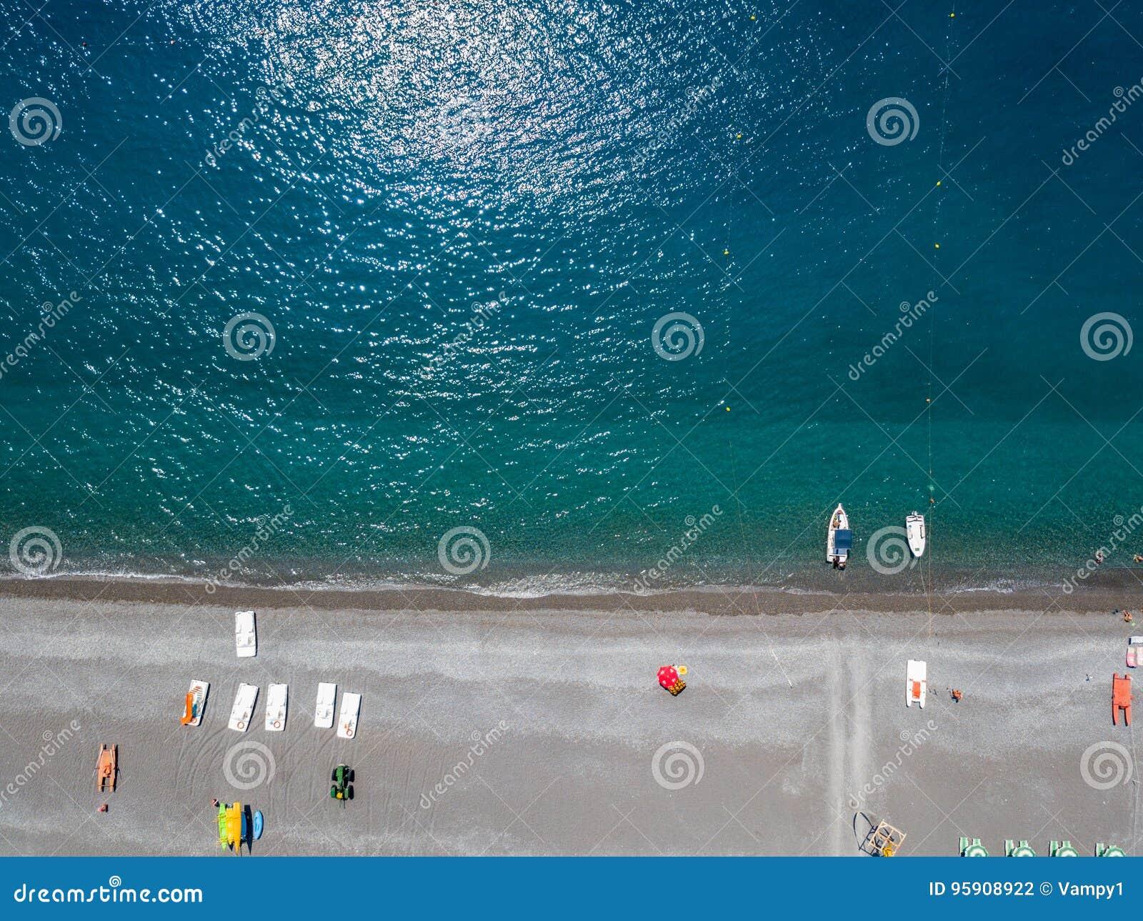 Flyg- sikt av en strand med kanoter, fartyg och paraplyer Praia en sto, landskap av Cosenza, Calabria, Italien