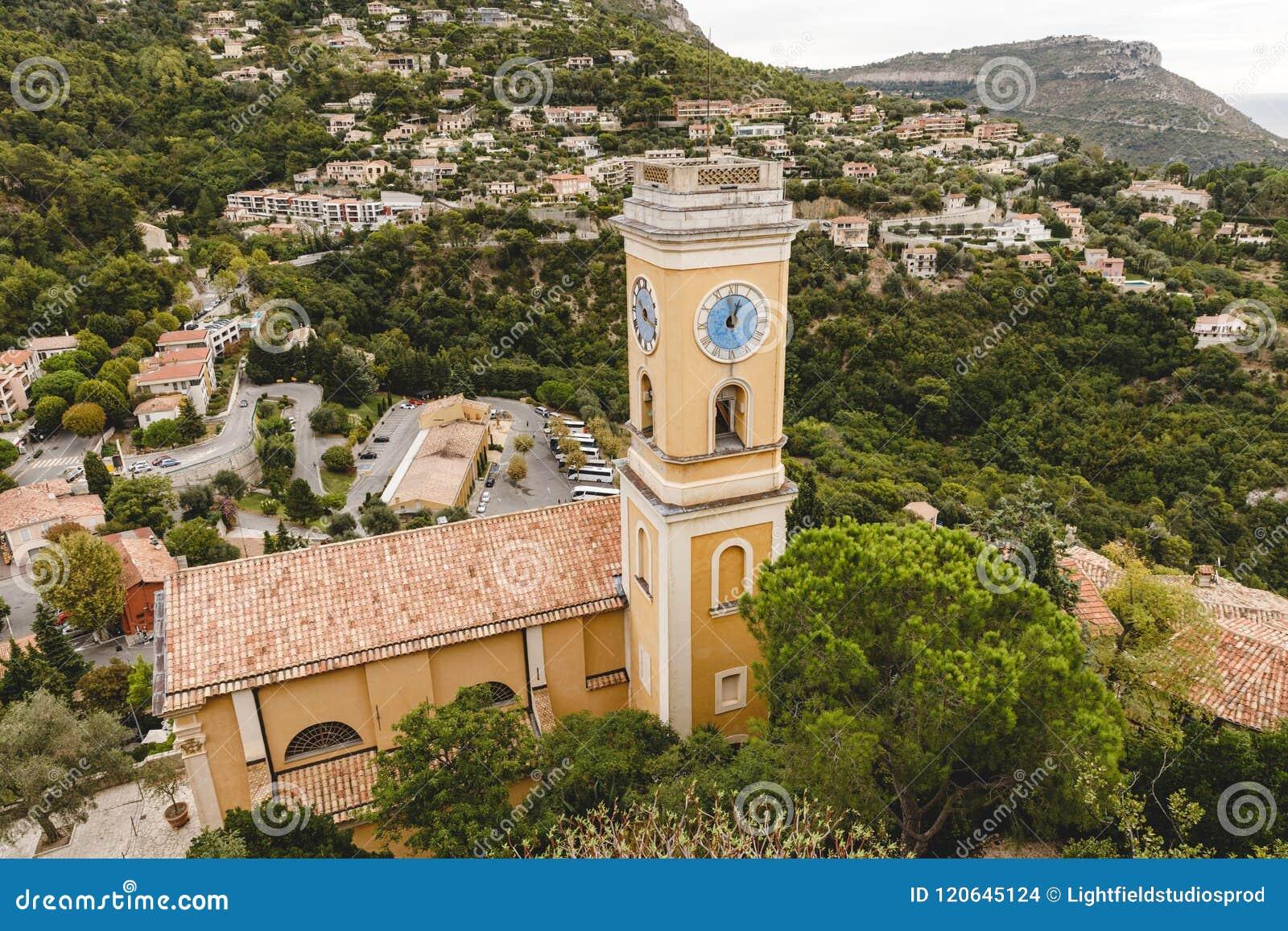 Flyg- sikt av kyrkan med klockatornet och klockan på den lilla europeiska staden på kullar,