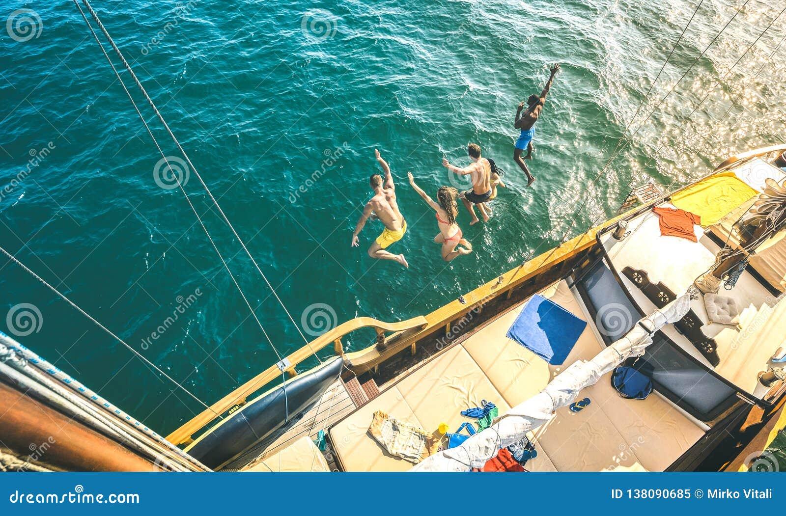 Flyg- sikt av lyckliga millenial vänner som tillsammans hoppar från segelbåten på havshavtur - rika grabbar och flickor som har g
