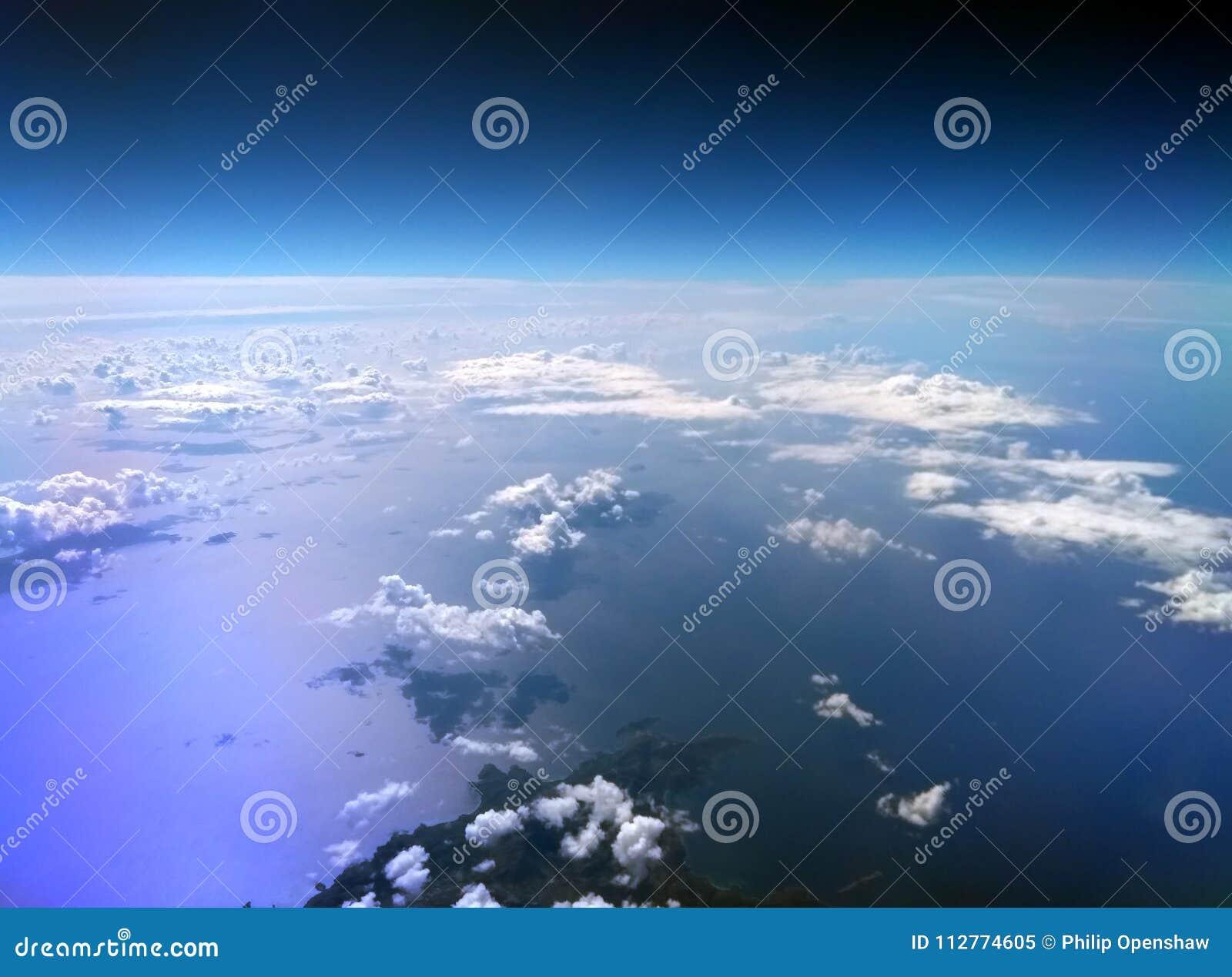 Flyg- sikt av medelhavet som tas från ett flygplan med mörker - blå himmel och moln reflekterade på vattnet och en ö