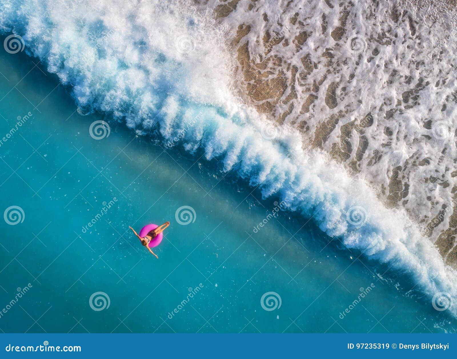 Flyg- sikt av simning för ung kvinna på den rosa badcirkeln