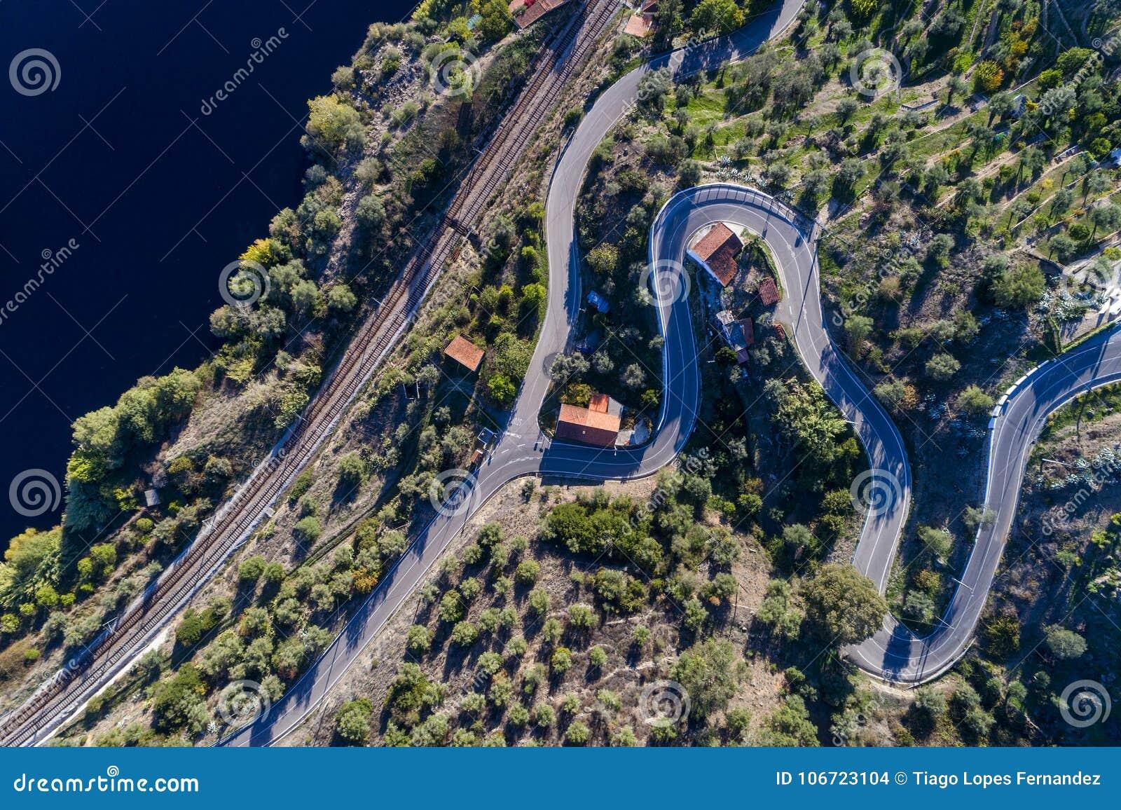 Flyg- sikt av spår för en slingrig väg och drevlängs Taguset River nära byn av Belver i Portugal