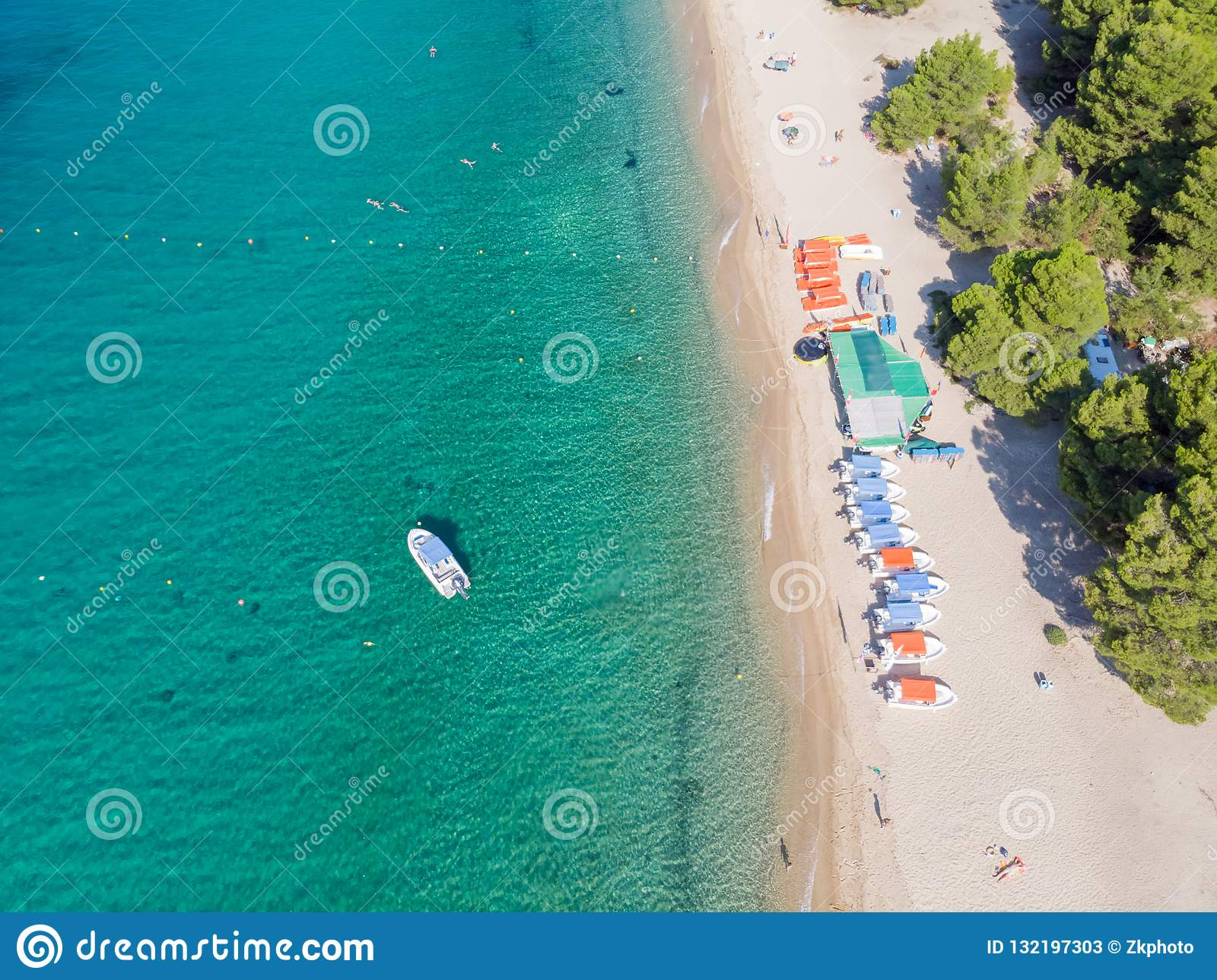Flyg- sikt för surr av havskusten, den sandiga stranden och blått vatten Fartyg nära stranden med lotten av parasoller