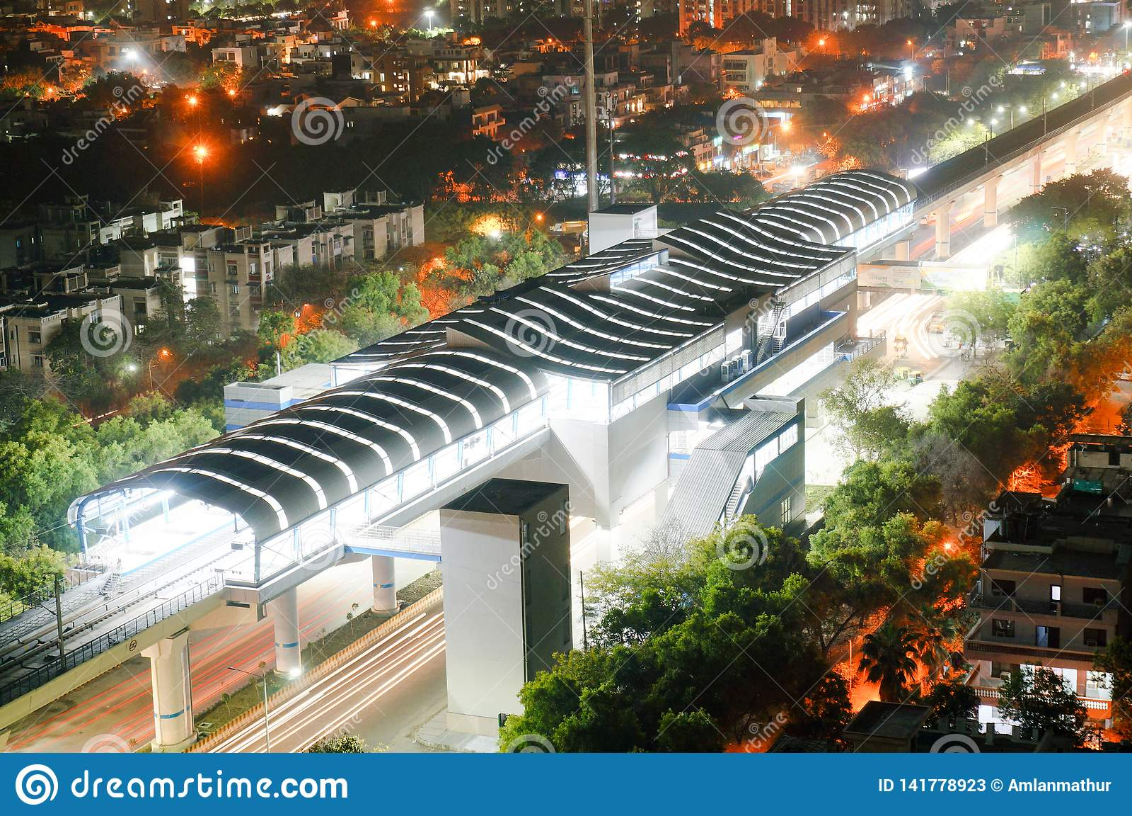 Flyg- skott av den tända tunnelbanasationen med slingor från att lämna drevet och trafik